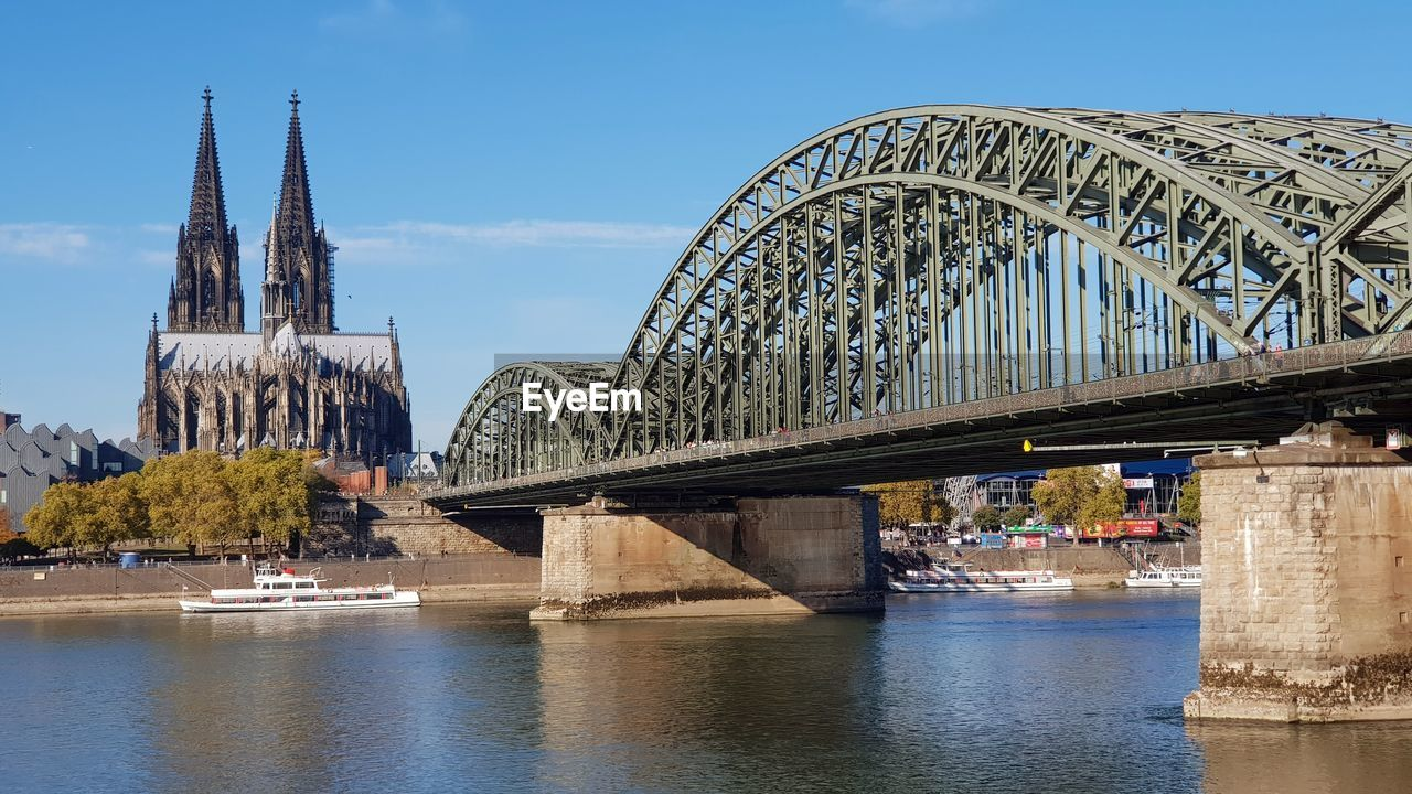 Hohenzollern bridge over river in city against sky