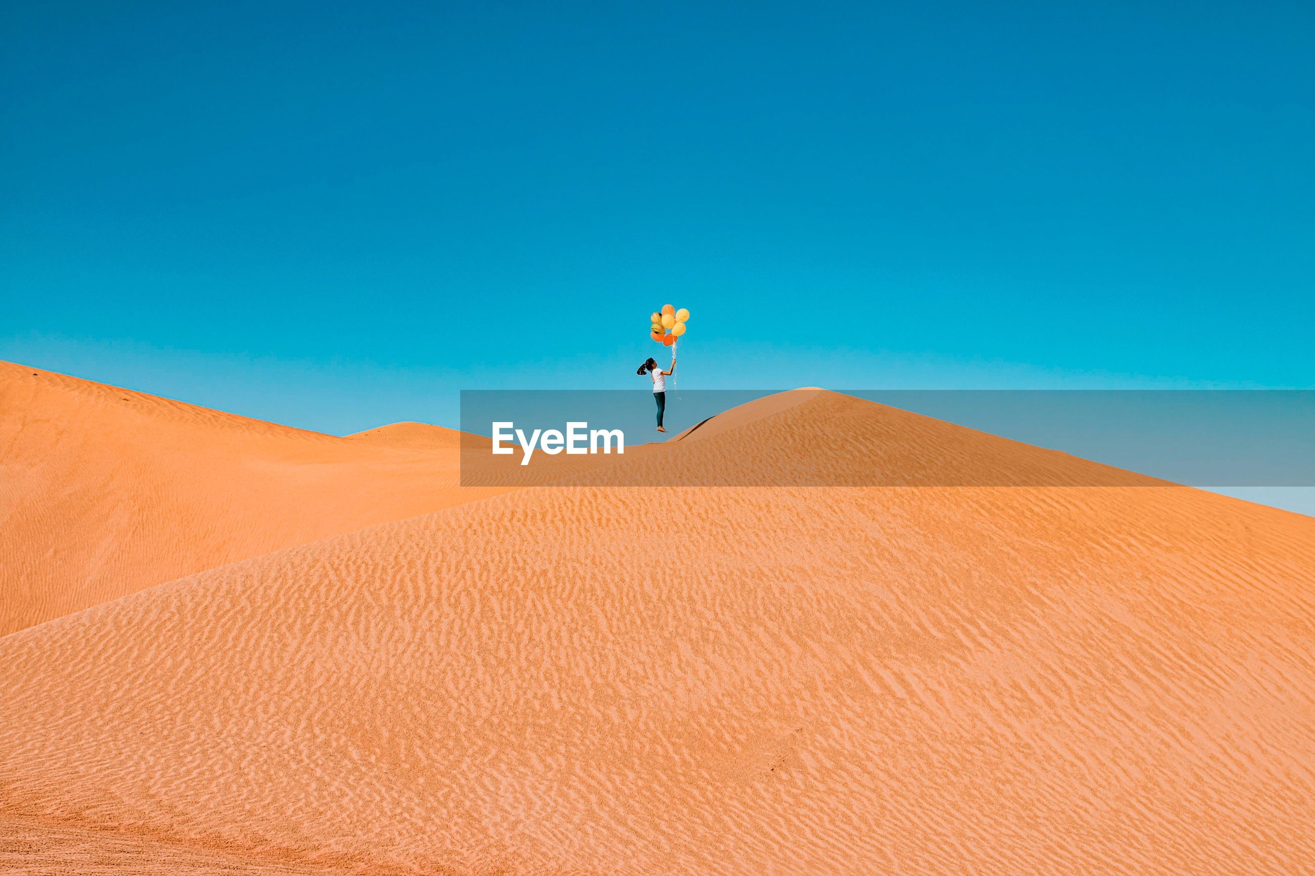 Low angle view of girl holding balloons while jumping on sand dune at desert