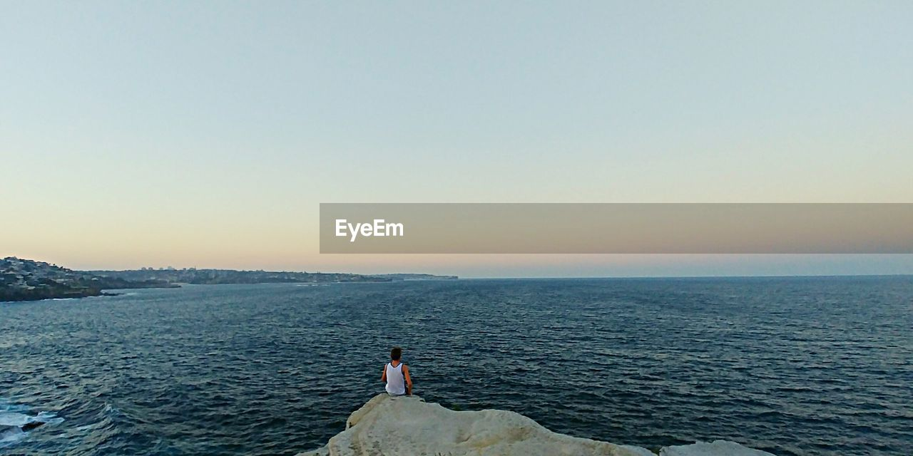 sky, sea, water, scenics - nature, beauty in nature, leisure activity, lifestyles, clear sky, copy space, real people, horizon, one person, nature, tranquility, tranquil scene, idyllic, horizon over water, non-urban scene, outdoors, looking at view