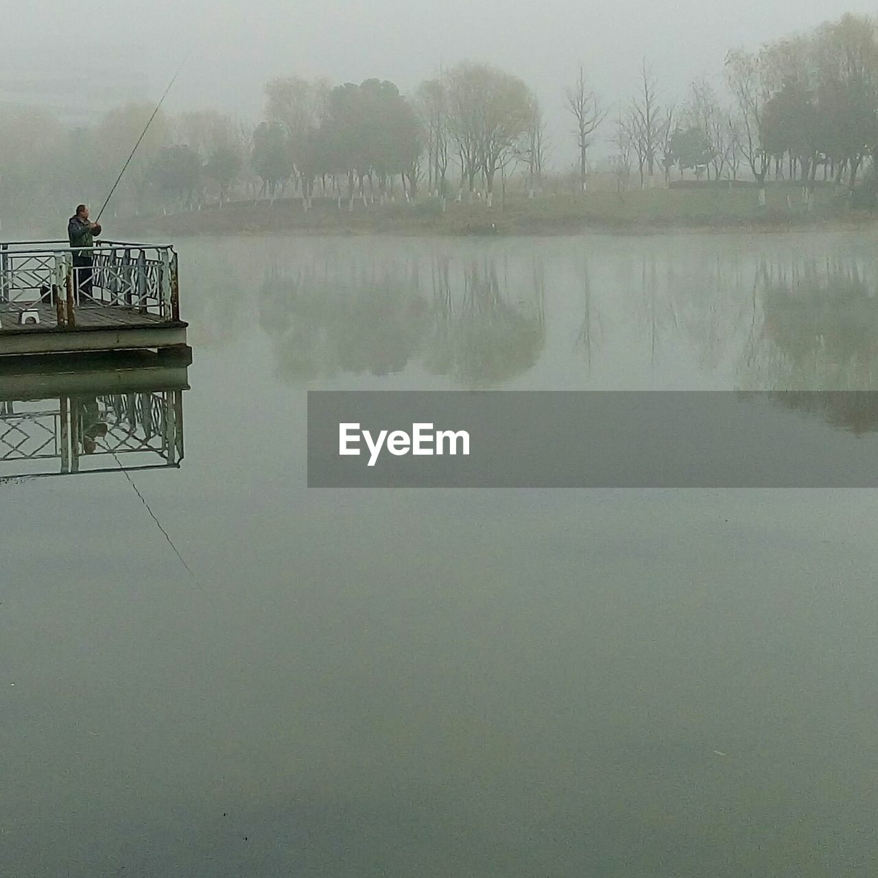 Man Standing On Pier And Fishing At Lake In Foggy Weather