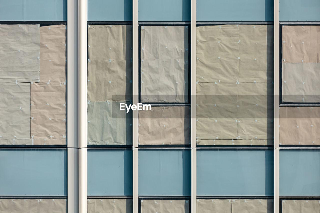 Beautiful texture of glass windows of condominium with crumple paper attachment for sun blocking