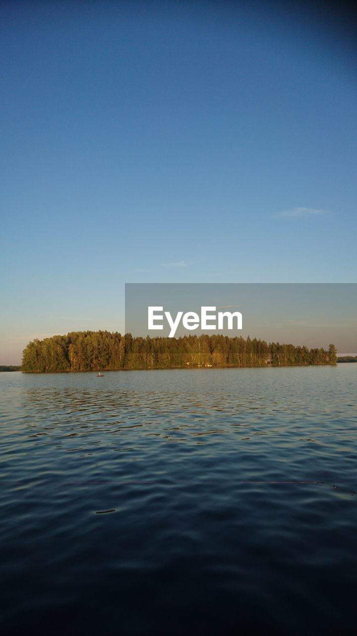 water, sky, tranquil scene, tranquility, scenics - nature, beauty in nature, waterfront, clear sky, lake, nature, copy space, no people, non-urban scene, plant, tree, idyllic, blue, day, outdoors