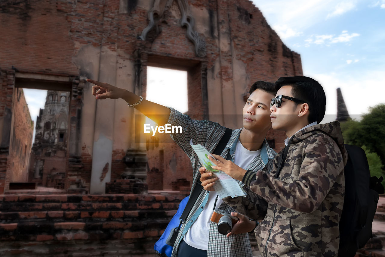 Young man pointing holding map and standing against built structure