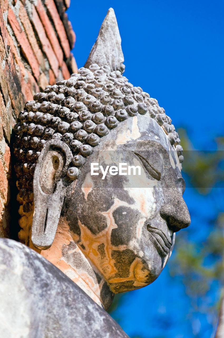 Low angle view of damaged buddha statue against sky
