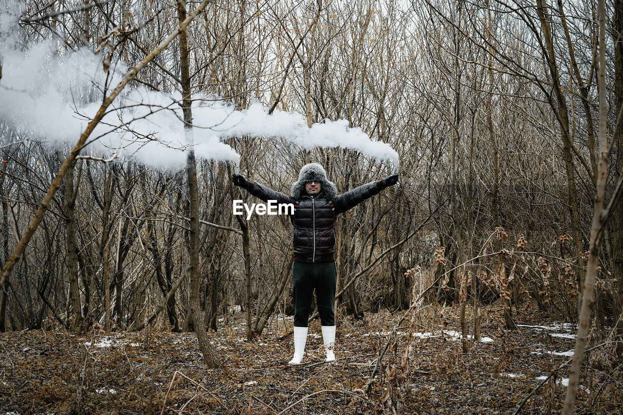 tree, human arm, one person, land, real people, leisure activity, winter, forest, front view, plant, nature, lifestyles, limb, bare tree, warm clothing, arms outstretched, cold temperature, standing, day, field, arms raised, outdoors, woodland, freedom