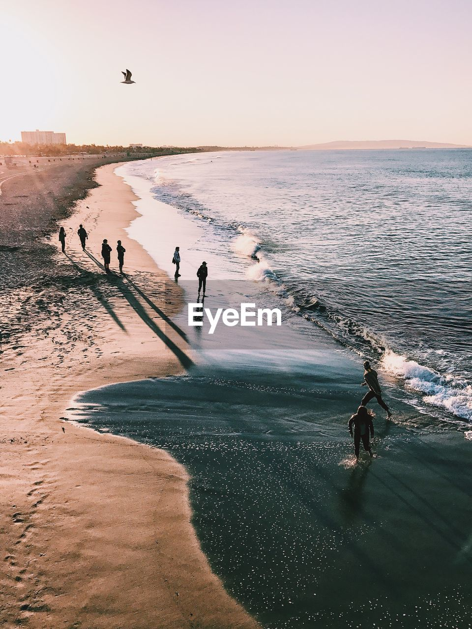 High Angle View Of People Enjoying At Beach Against Sky During Sunset