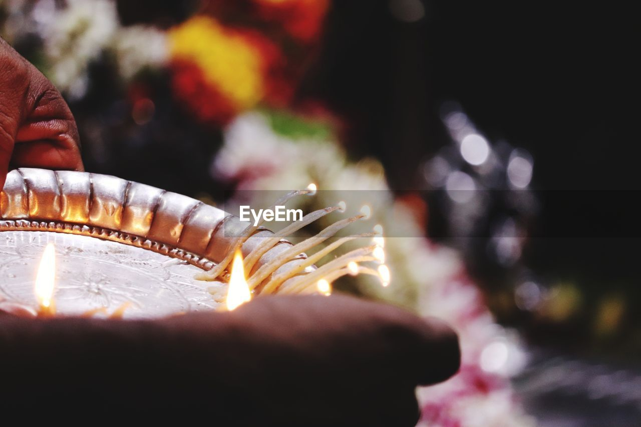 Close-Up Of Cropped Hands Holding Lit Diya