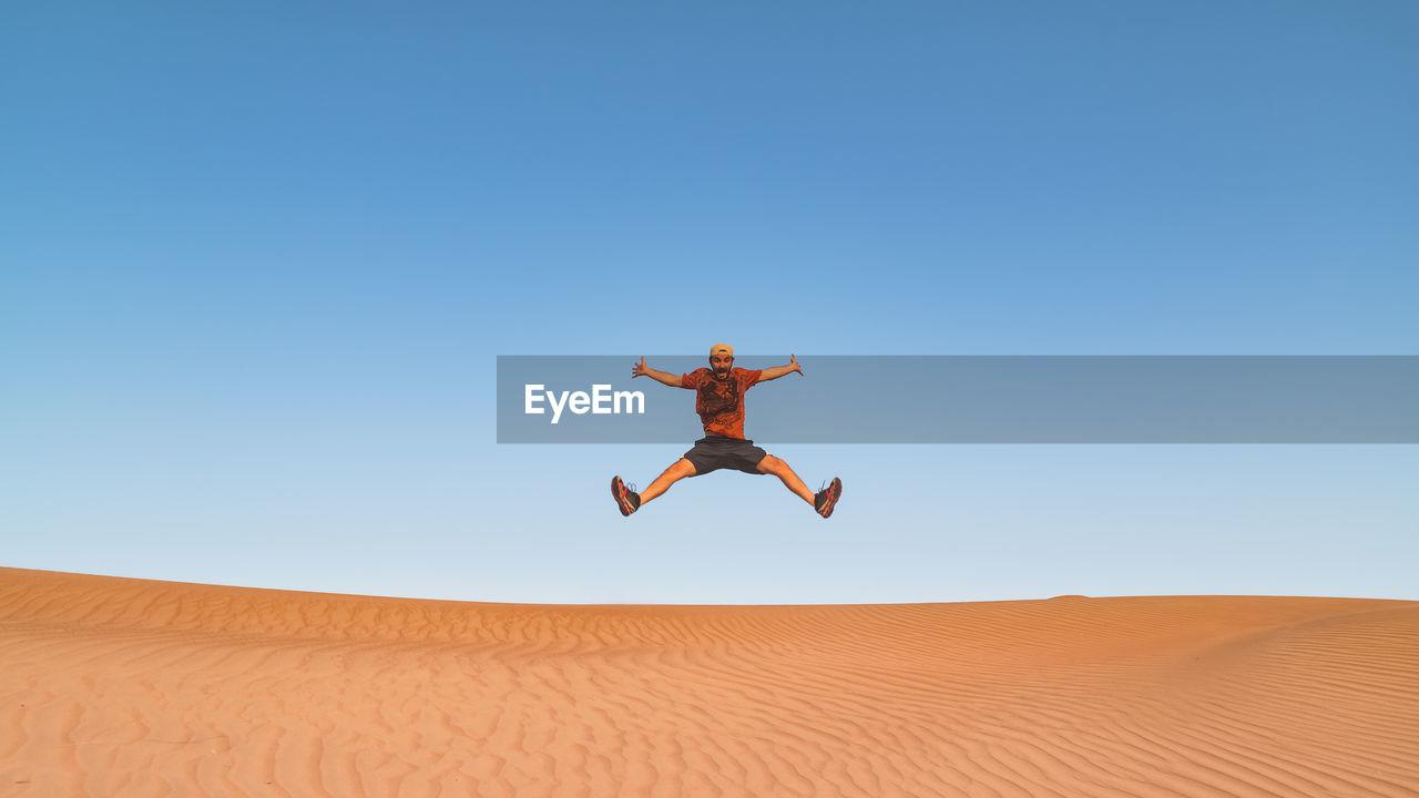 Man jumping in desert against clear sky