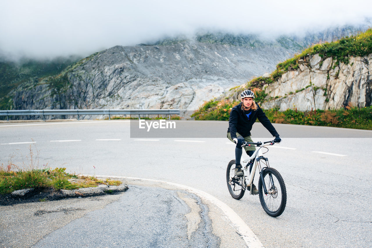 Cyclist Riding On Road Against Mountains During Foggy Weather