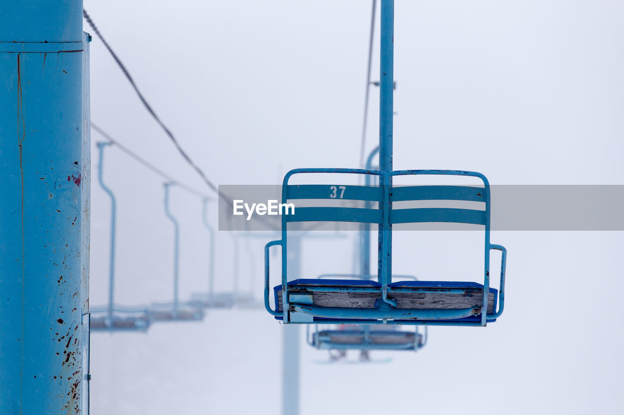 Low Angle View Of Ski Lift Over Snow Covered Field
