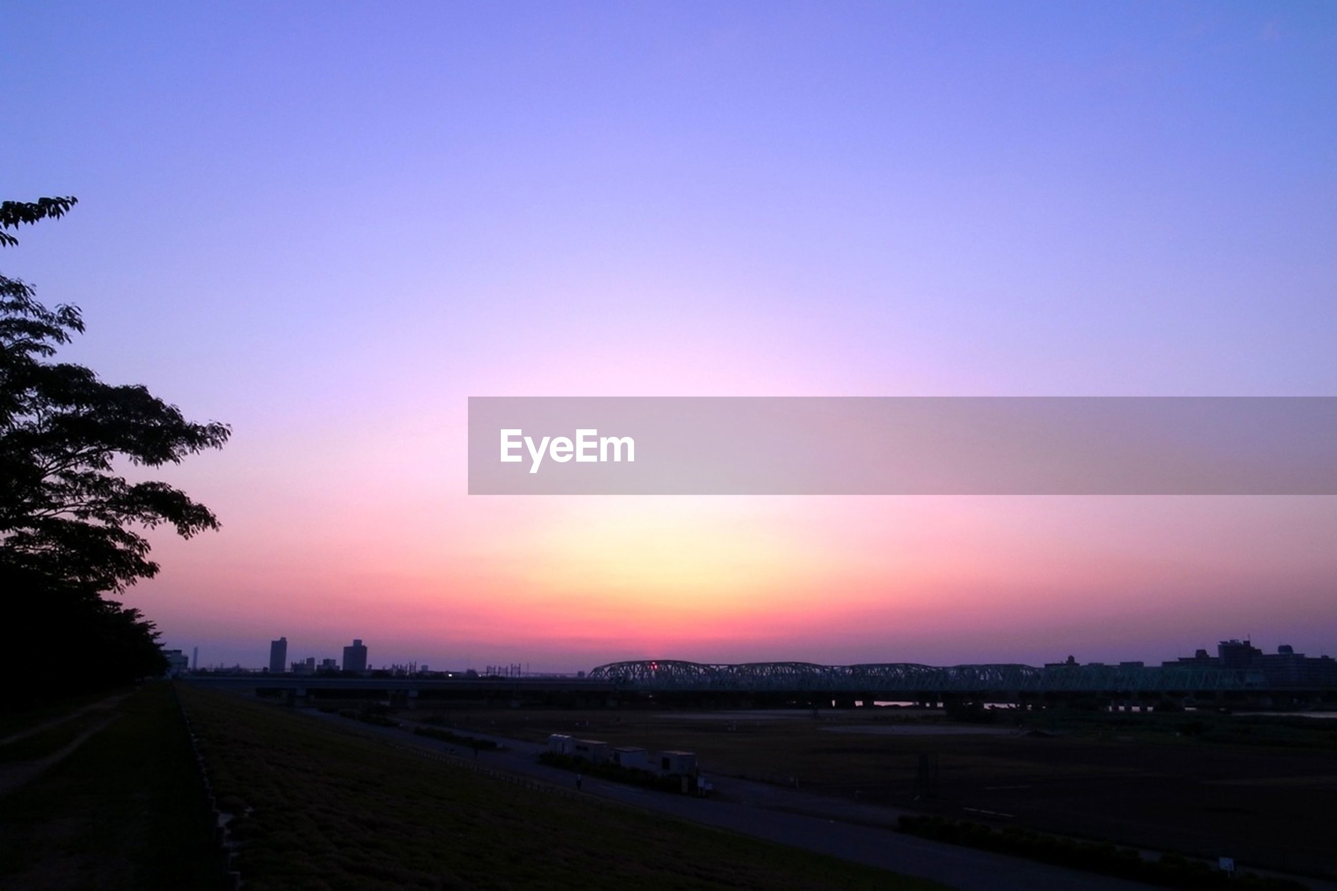 sunset, copy space, clear sky, road, transportation, the way forward, landscape, tranquility, silhouette, tranquil scene, sky, road marking, dusk, street, scenics, orange color, nature, field, tree, outdoors
