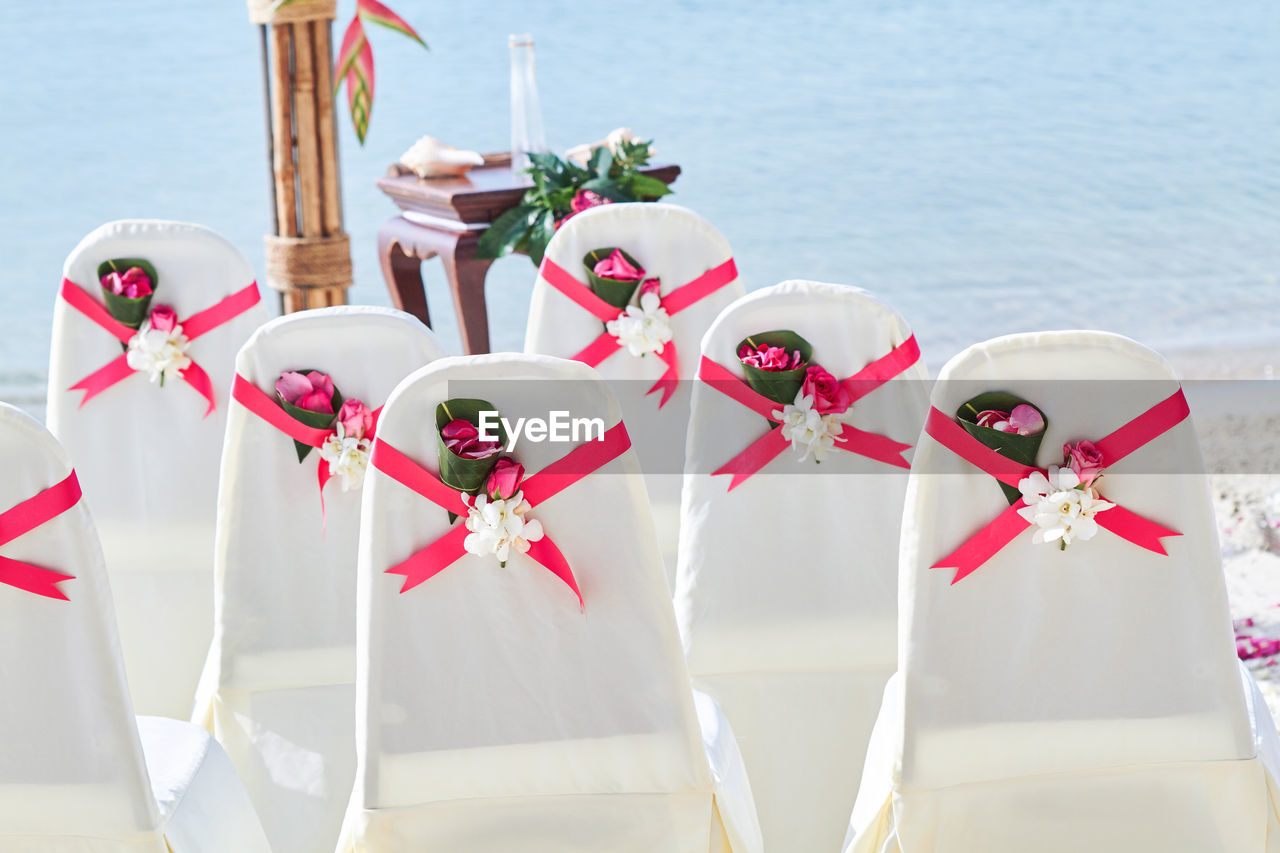 Empty chairs arranged at beach during celebration