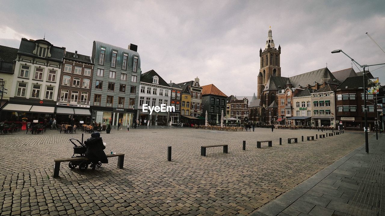 building exterior, architecture, built structure, sky, city, building, cobblestone, street, cloud - sky, sitting, nature, incidental people, seat, real people, residential district, city life, lifestyles, men, footpath, people, outdoors, paving stone