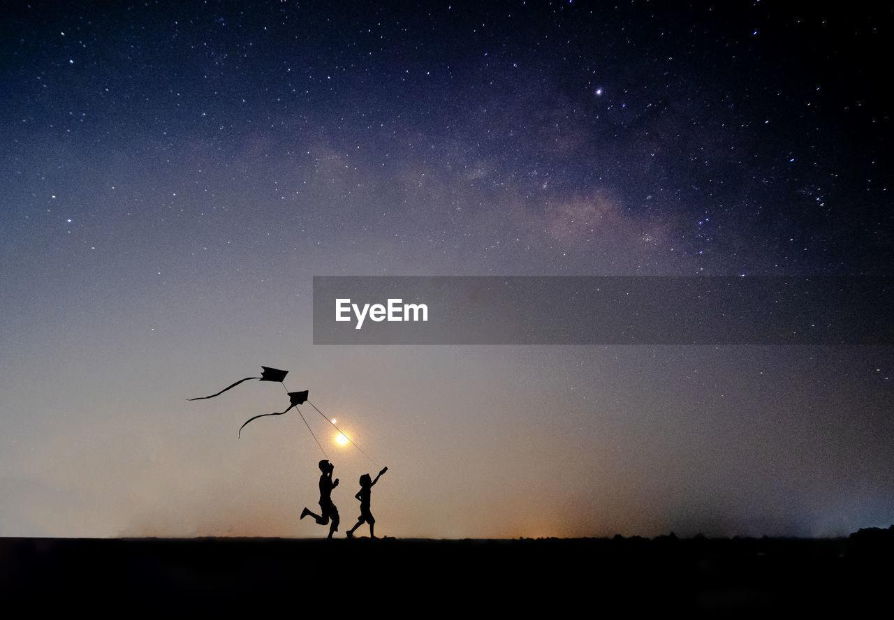 Silhouette people flying kite on field against sky at dusk