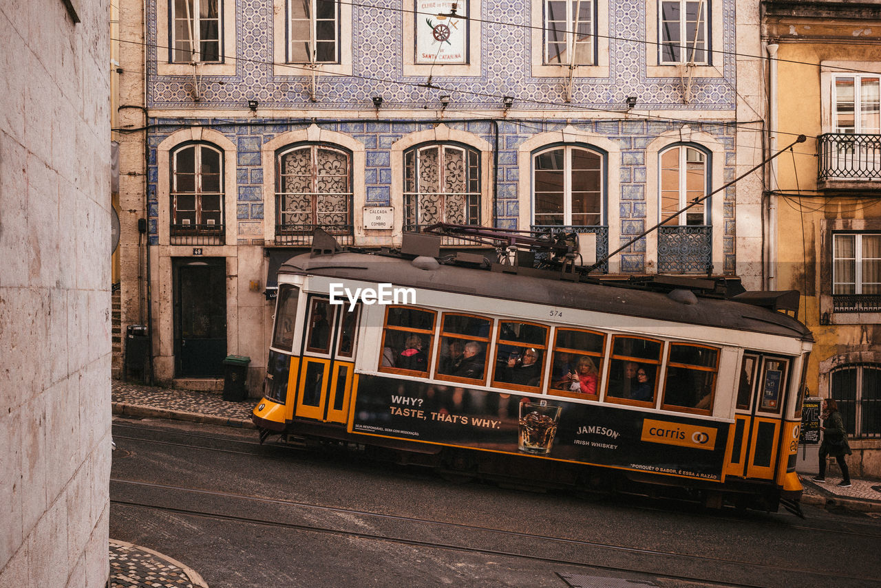 architecture, building exterior, built structure, mode of transportation, public transportation, cable car, transportation, city, window, day, building, land vehicle, railroad track, track, yellow, street, travel, outdoors, rail transportation, no people, school bus