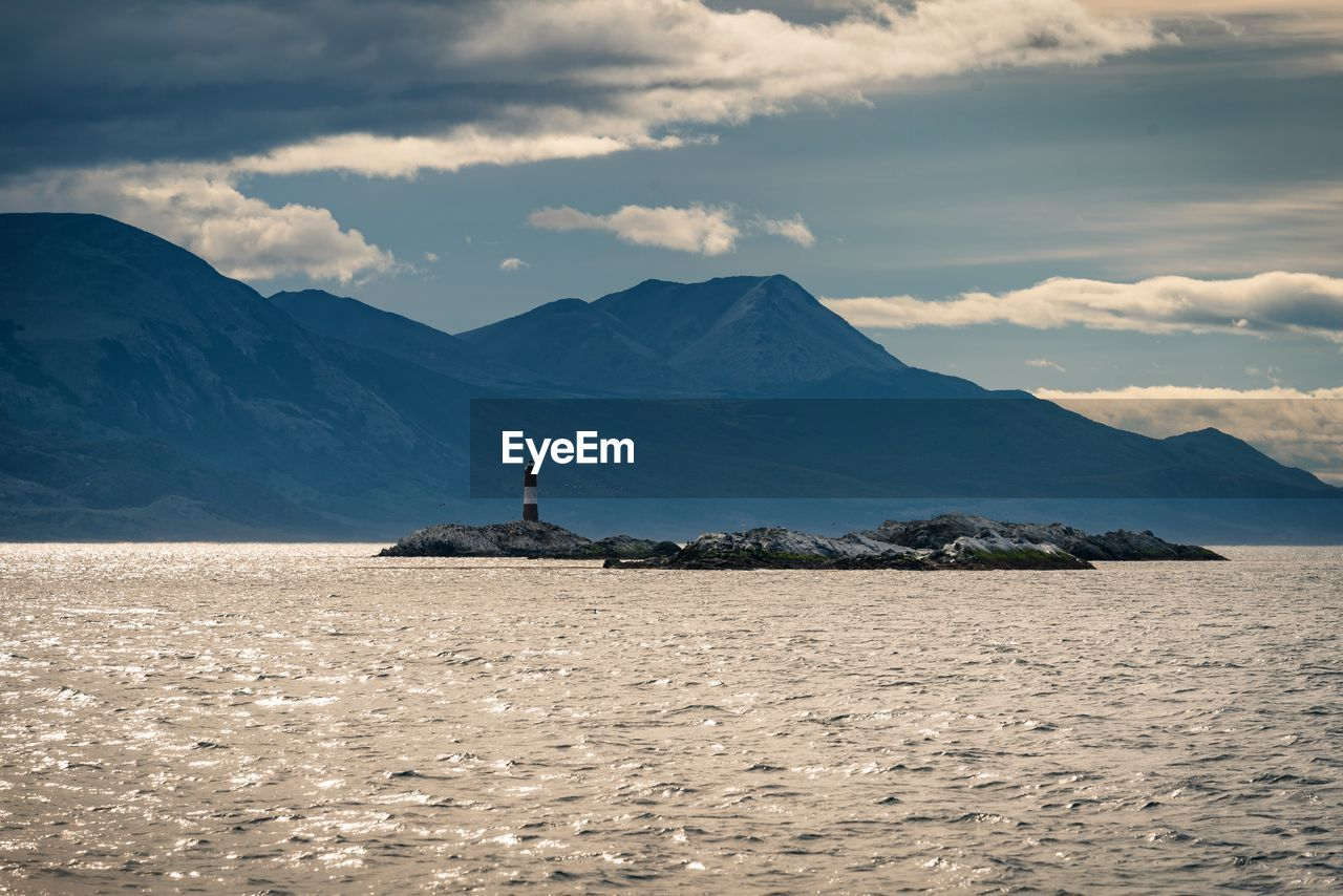 SCENIC VIEW OF SEA AND MOUNTAINS AGAINST CLOUDY SKY