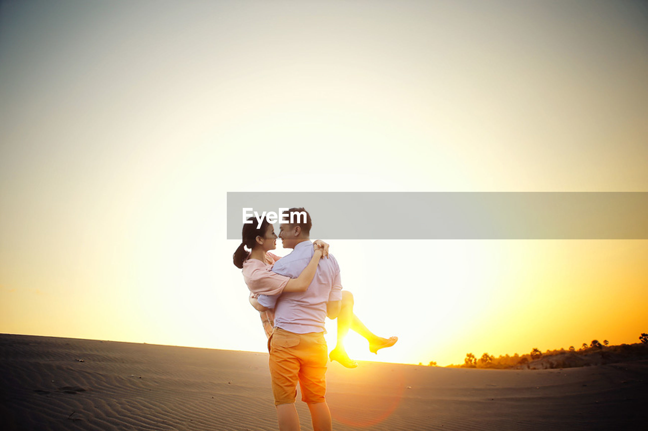 sunset, lifestyles, leisure activity, sun, clear sky, full length, copy space, standing, casual clothing, orange color, sunlight, rear view, men, childhood, boys, sky, holding