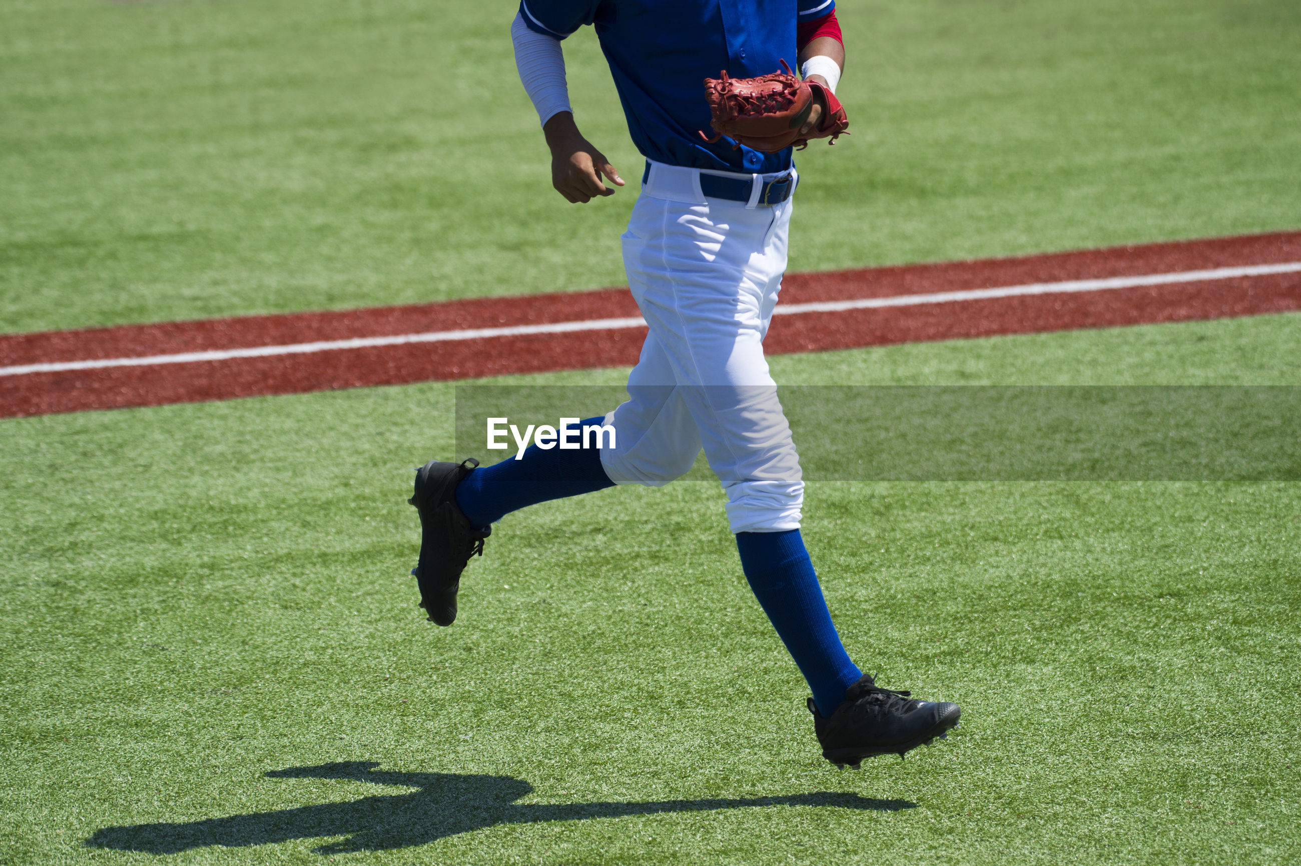 Low section of baseball player running on playing field