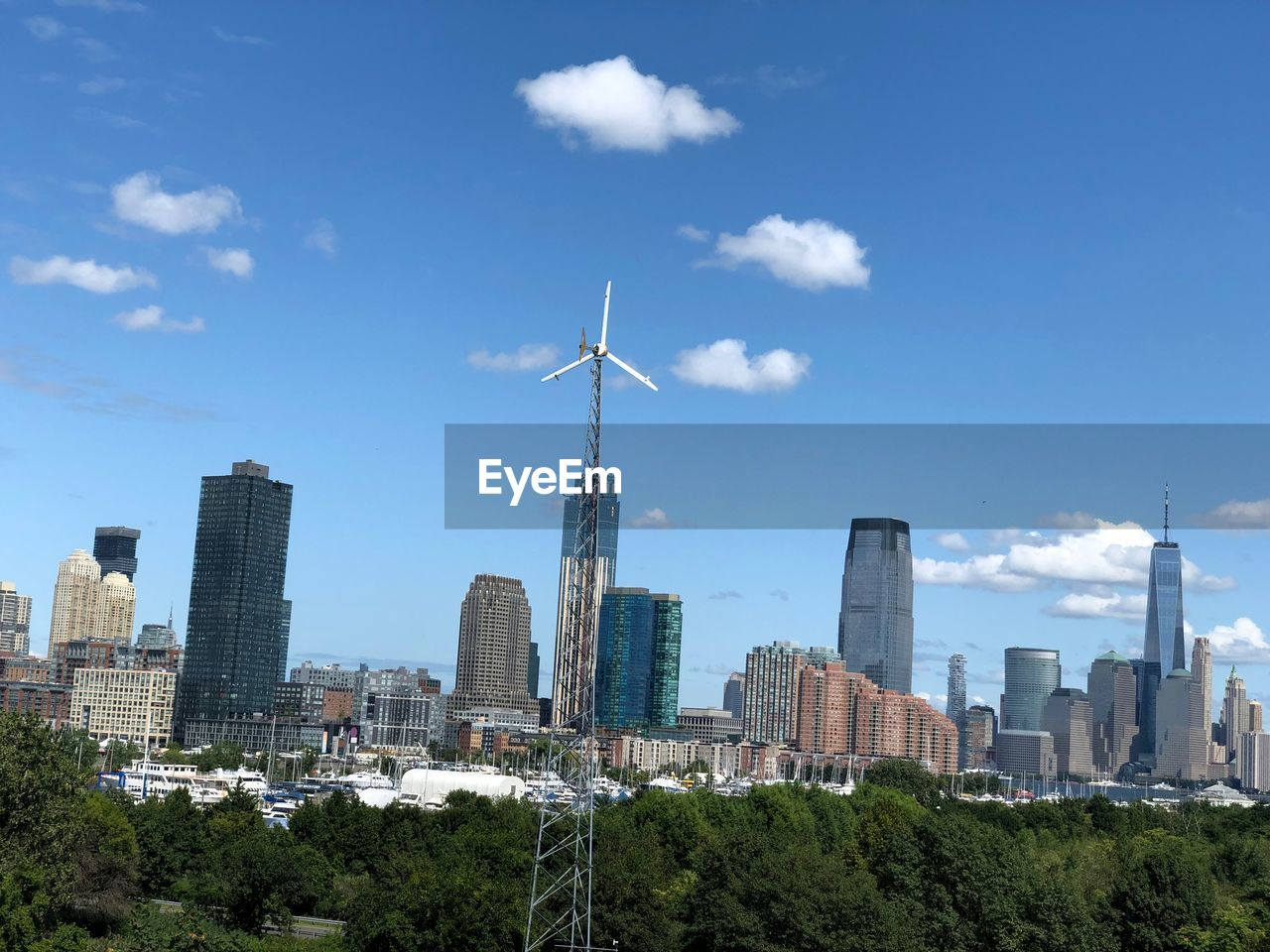 built structure, architecture, sky, building exterior, city, building, nature, cloud - sky, renewable energy, office building exterior, tower, day, tall - high, environmental conservation, no people, skyscraper, alternative energy, landscape, fuel and power generation, tree, cityscape, outdoors, modern, spire, financial district