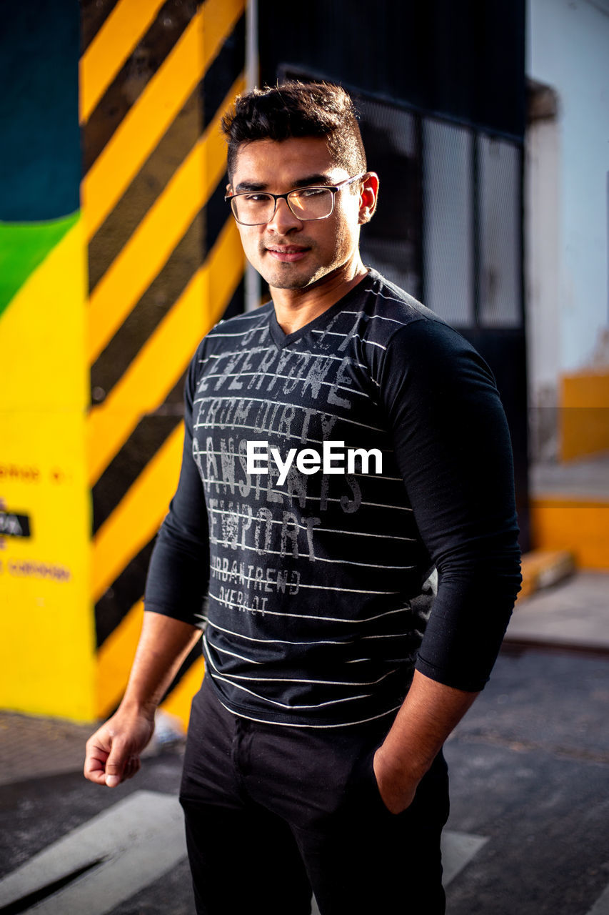one person, three quarter length, real people, looking at camera, young men, portrait, young adult, lifestyles, front view, casual clothing, leisure activity, standing, glasses, smiling, architecture, black color, focus on foreground
