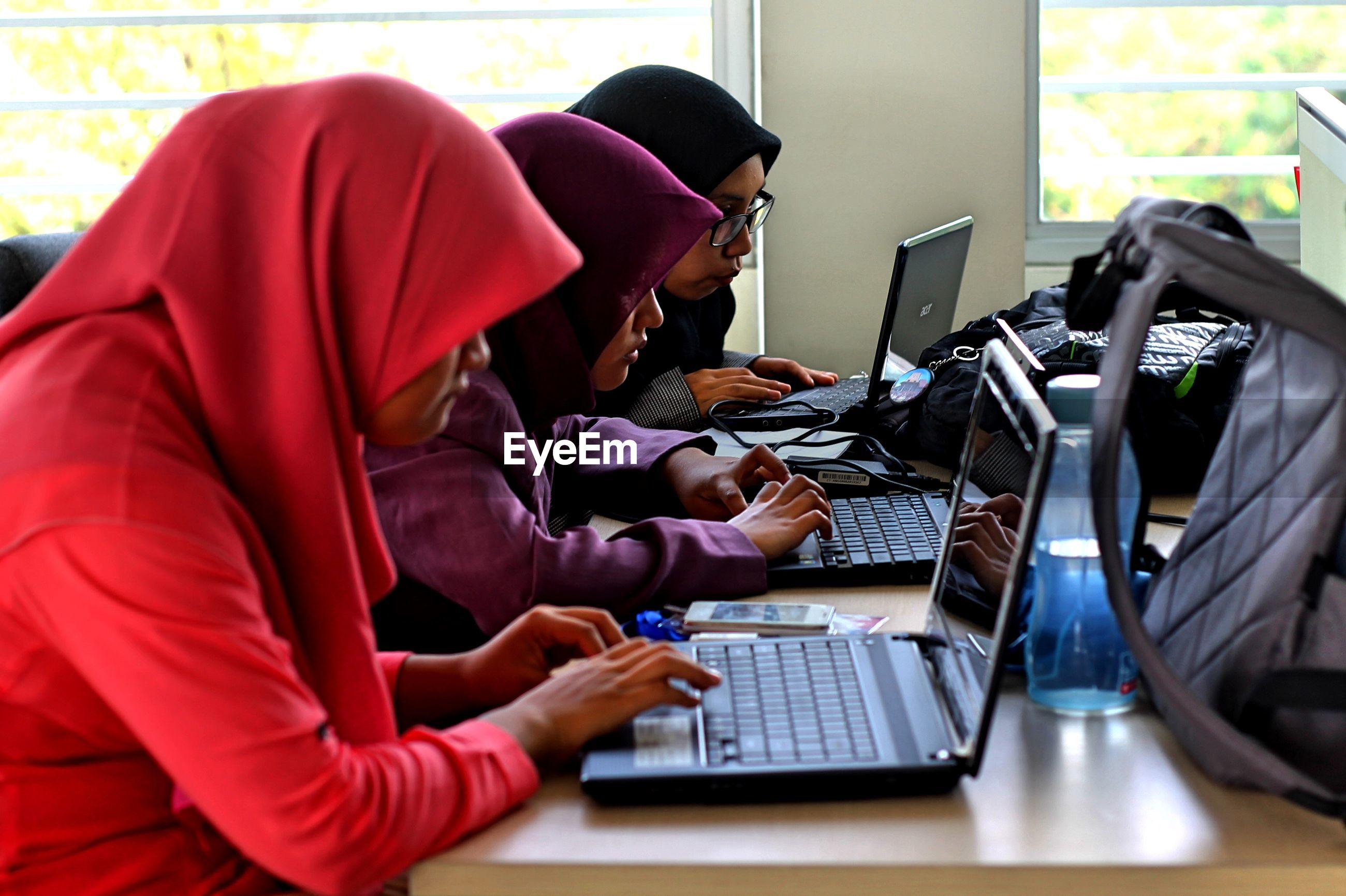 High angle view of young women using laptops on table