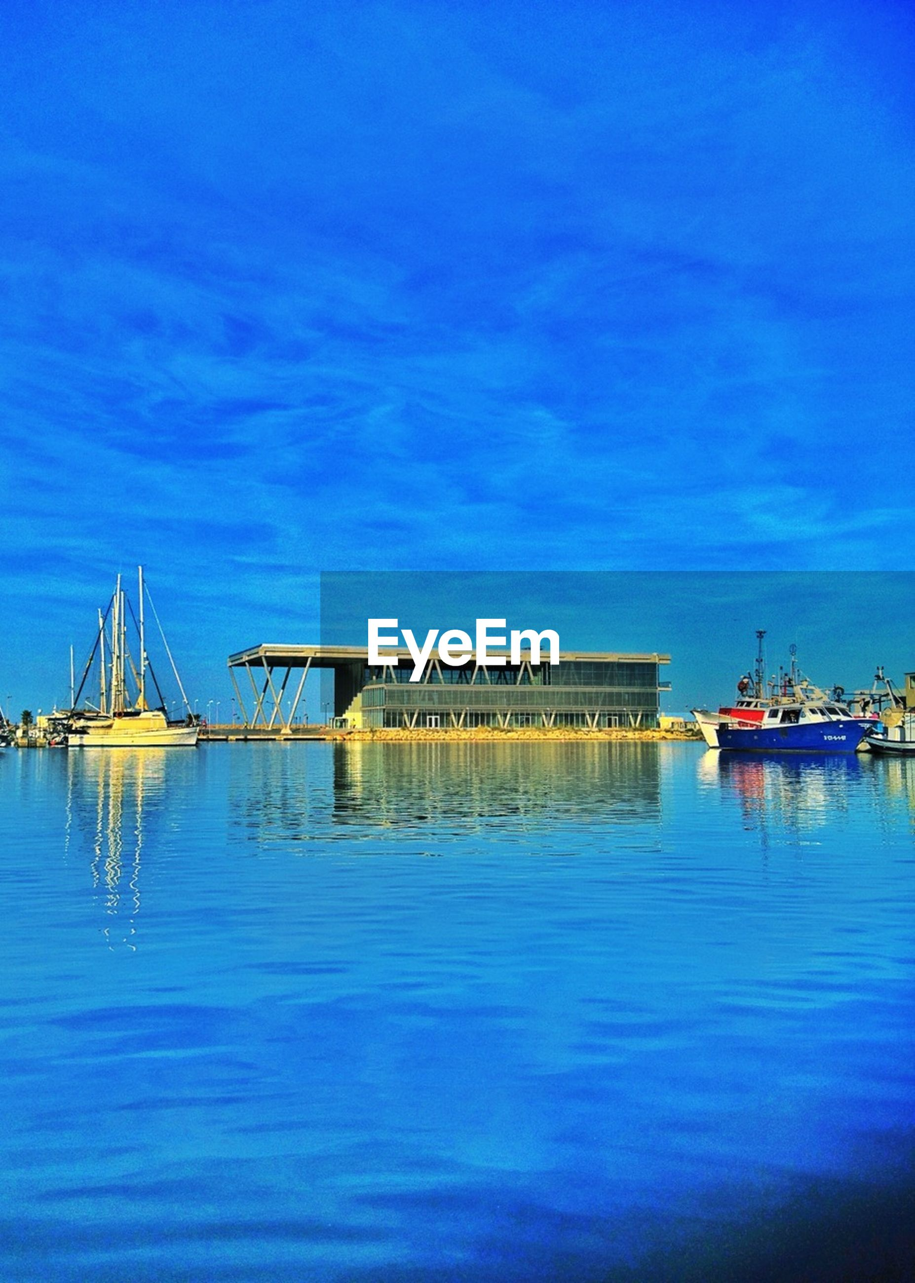 blue, water, waterfront, sea, sky, nautical vessel, harbor, tranquility, pier, transportation, built structure, moored, tranquil scene, reflection, boat, nature, scenics, cloud, mode of transport, outdoors