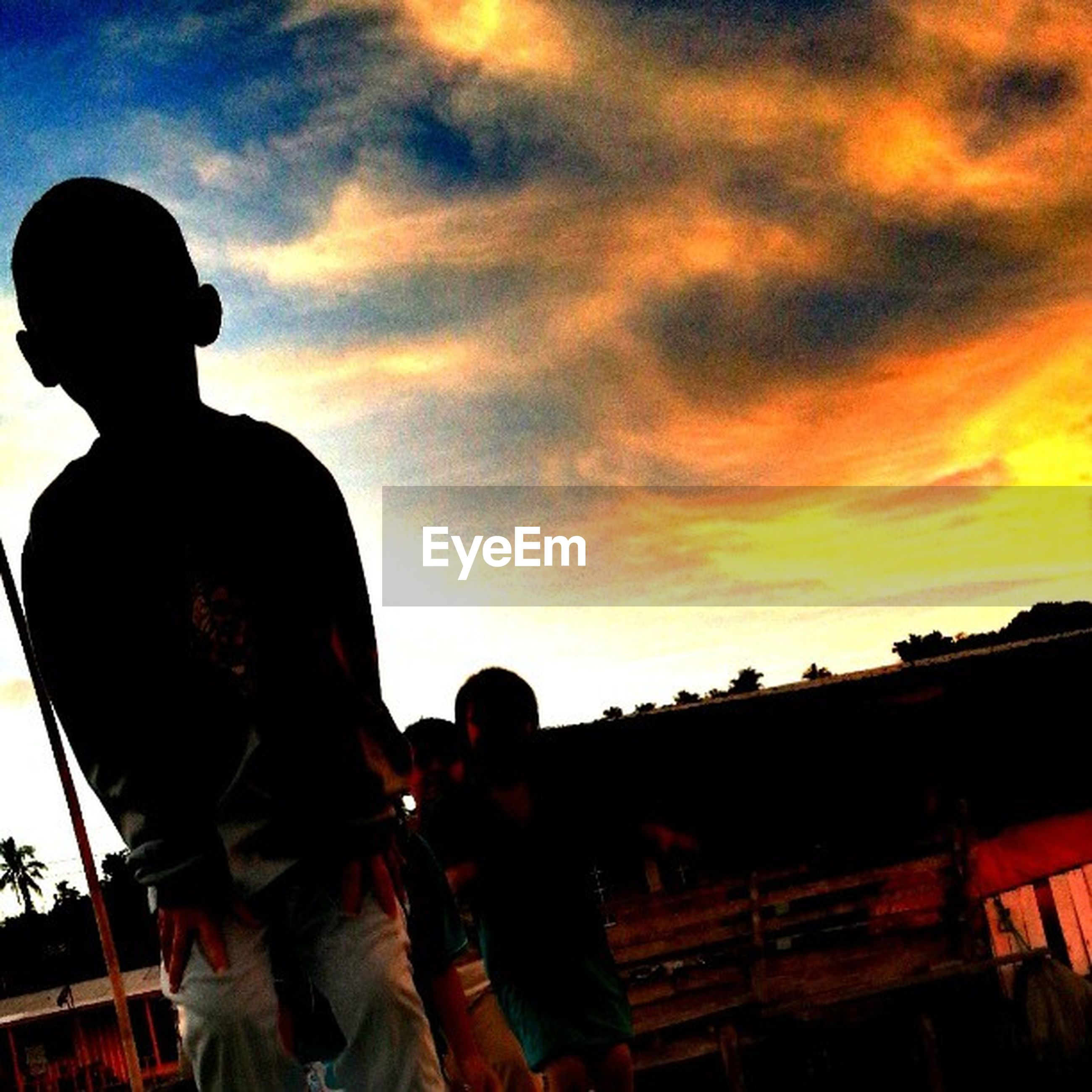 lifestyles, sky, sunset, leisure activity, cloud - sky, standing, silhouette, three quarter length, photography themes, waist up, photographing, togetherness, men, casual clothing, camera - photographic equipment, rear view, love