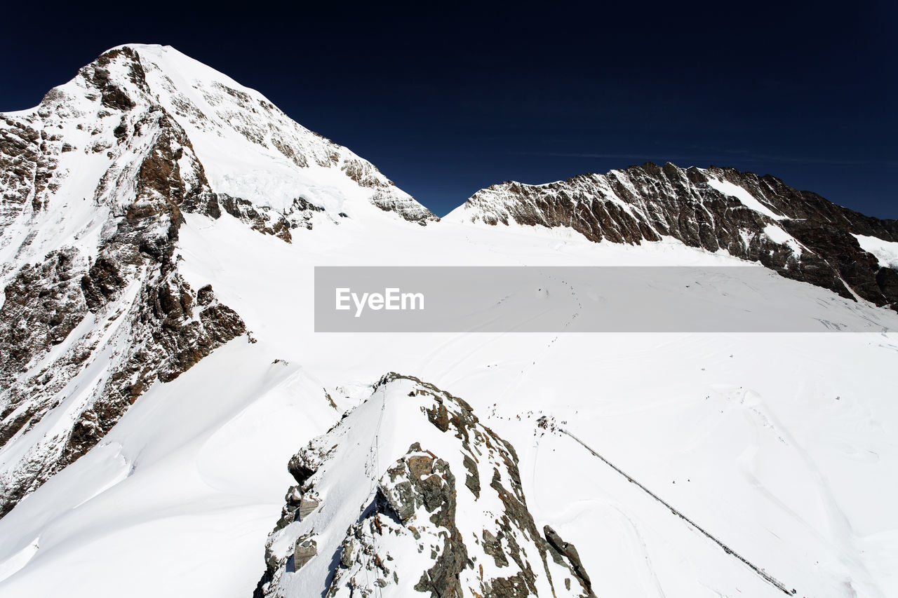 snow, mountain, cold temperature, winter, snowcapped mountain, beauty in nature, nature, tranquility, mountain range, tranquil scene, white color, scenics, weather, majestic, physical geography, outdoors, non-urban scene, day, mountain peak, clear sky, landscape, no people, sky, extreme sports