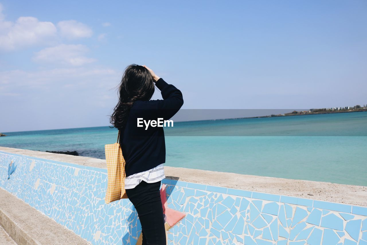 Side View Of Woman Looking At Sea While Standing By Retaining Wall Against Blue Sky During Sunny Day