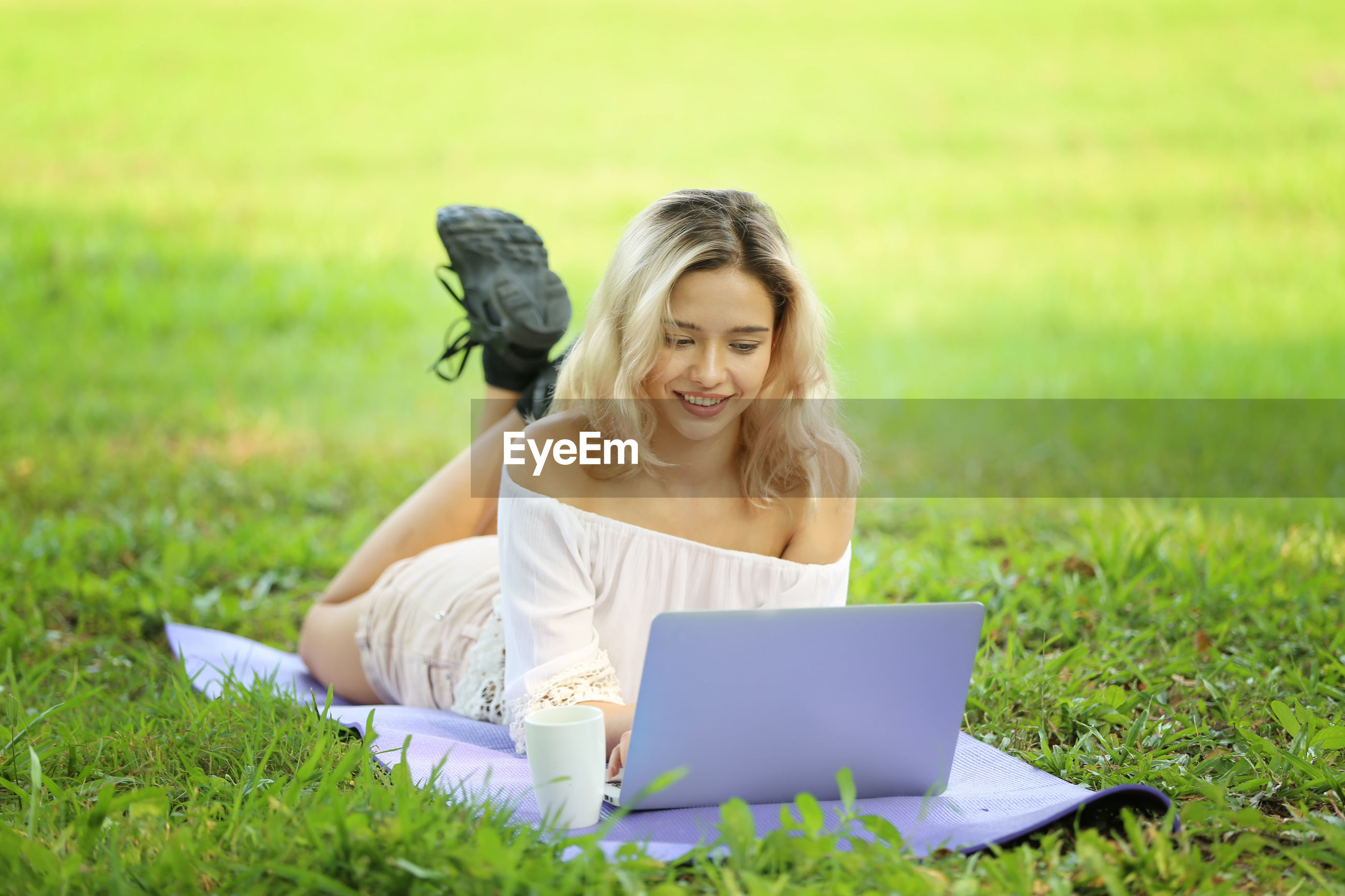 Smiling young woman using laptop while relaxing at park