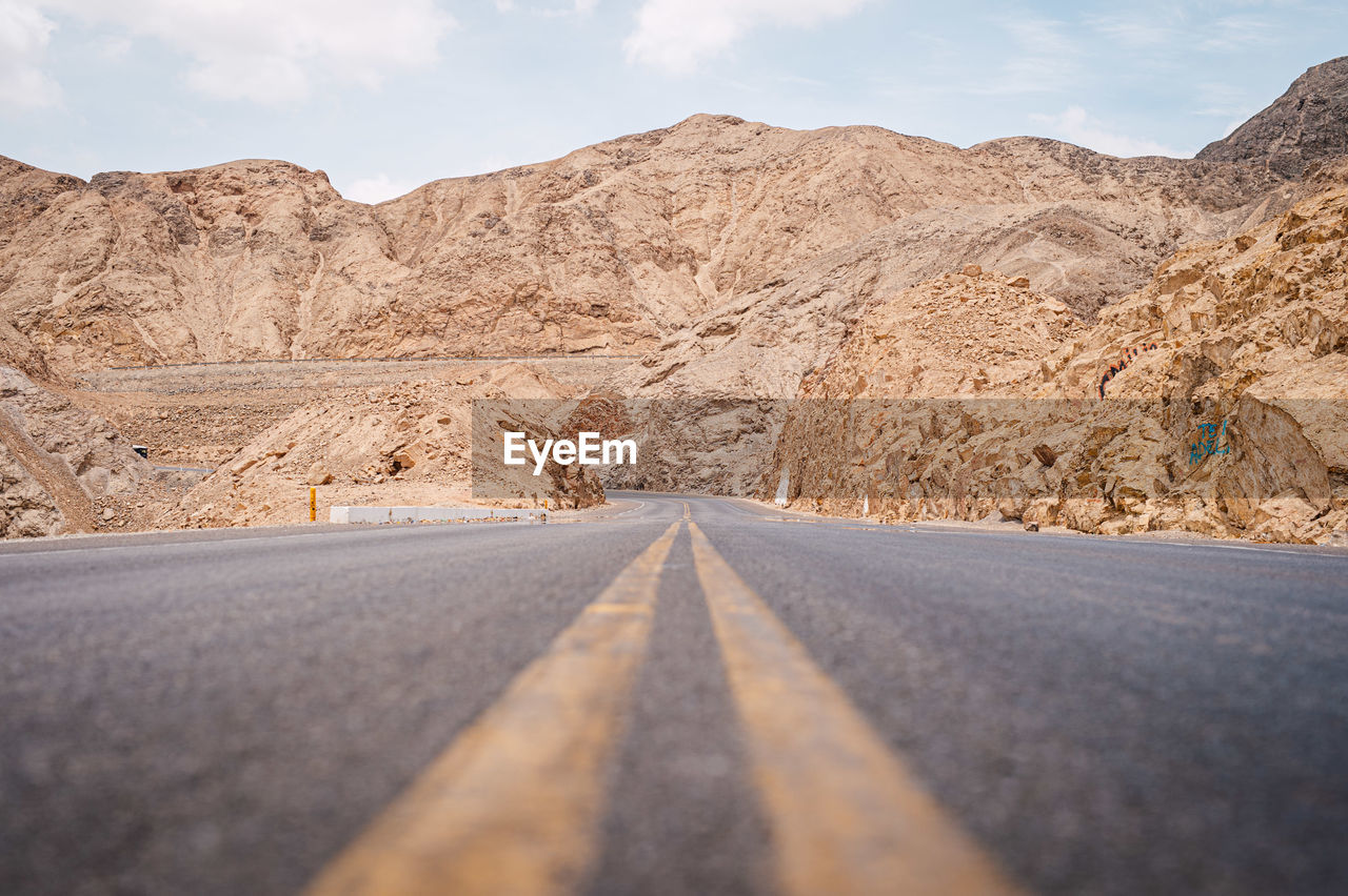 road, mountain, direction, the way forward, transportation, scenics - nature, beauty in nature, mountain range, road marking, diminishing perspective, marking, symbol, sky, sign, nature, non-urban scene, empty road, no people, landscape, tranquil scene, arid climate, climate, outdoors, formation, surface level