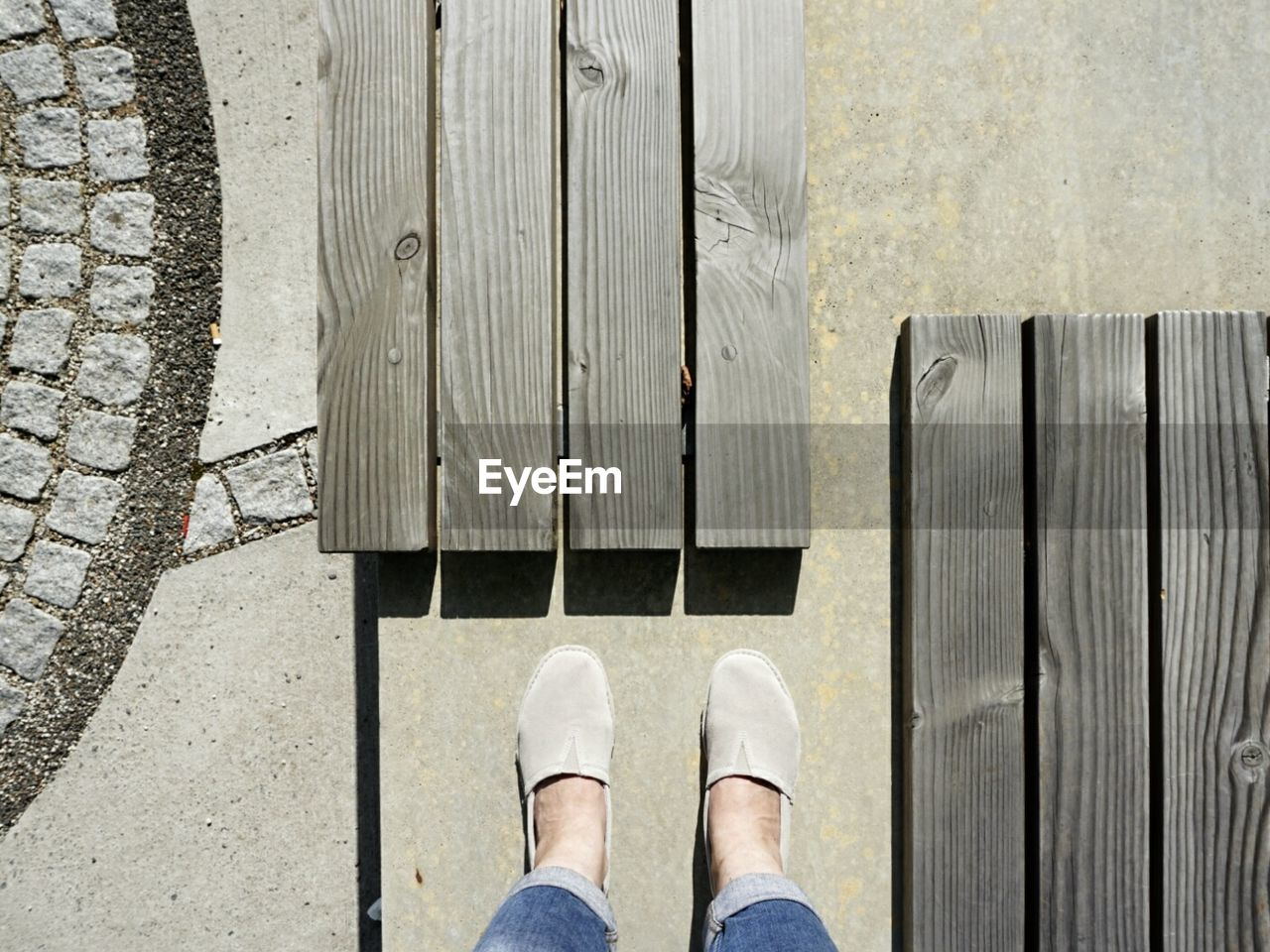 LOW SECTION OF PERSON STANDING ON WOODEN SURFACE
