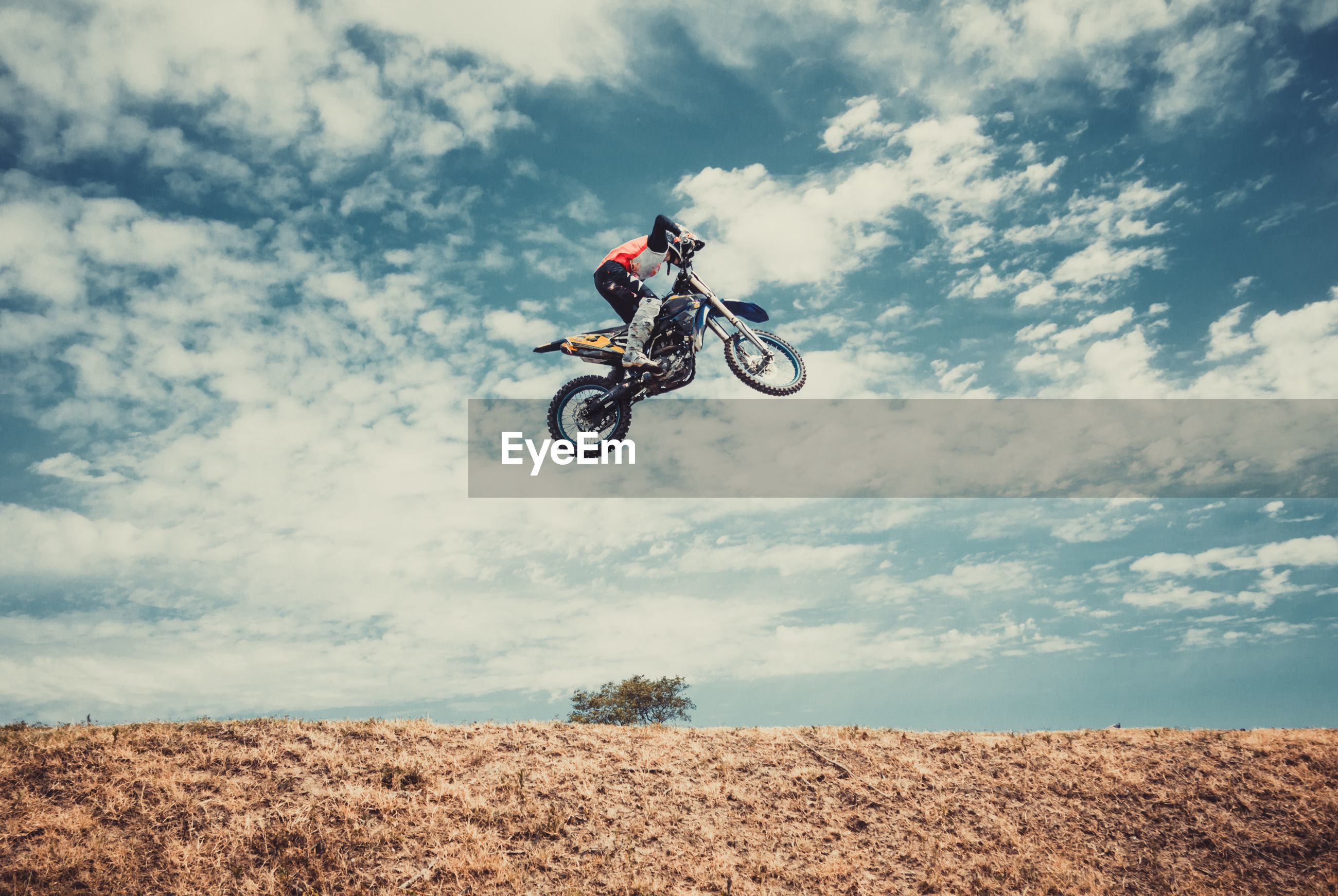 Low angle view of man jumping while riding motorcycle against sky