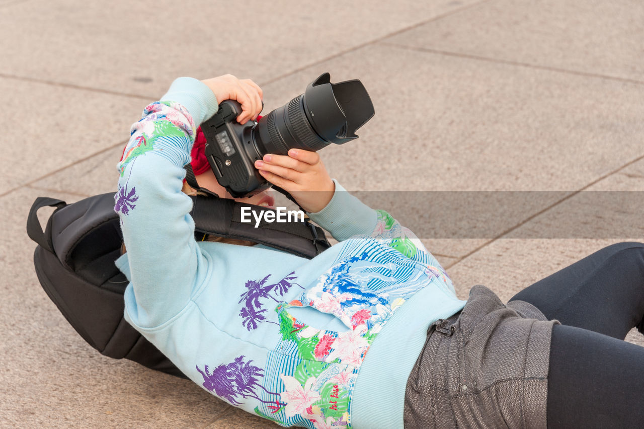 LOW SECTION OF WOMAN PHOTOGRAPHING ON CAMERA