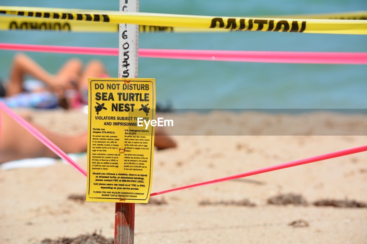 CLOSE-UP OF SIGN BOARD ON BEACH