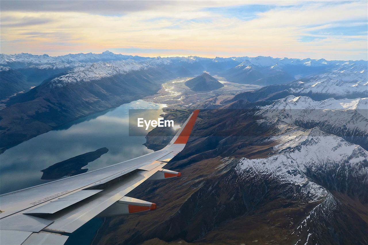 airplane, air vehicle, cloud - sky, scenics - nature, beauty in nature, cold temperature, sky, mountain, winter, aircraft wing, transportation, snow, no people, mode of transportation, environment, flying, nature, mountain range, snowcapped mountain, outdoors, mountain peak, plane