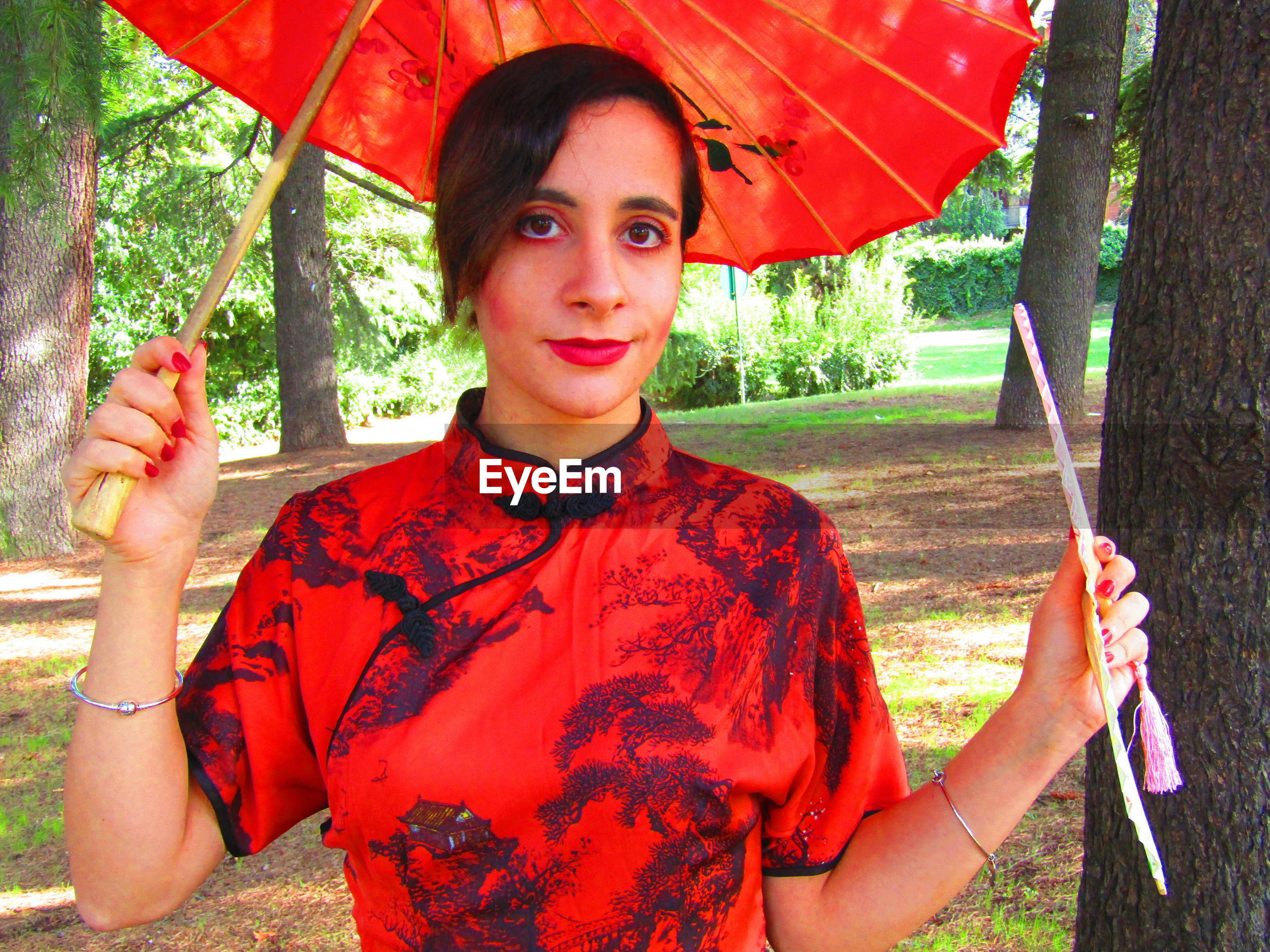 Portrait of woman holding red umbrella while standing outdoors