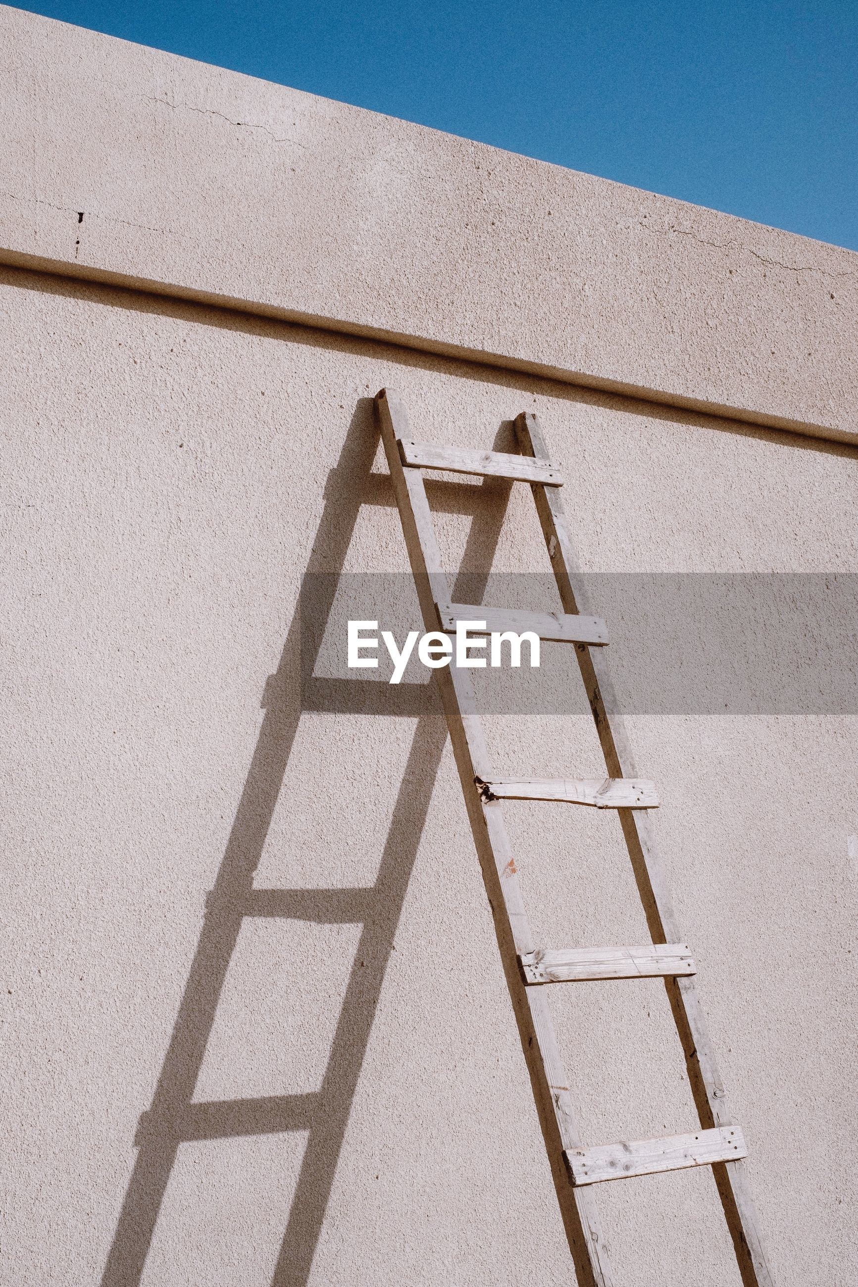 Low angle view of ladder on building wall during sunny day