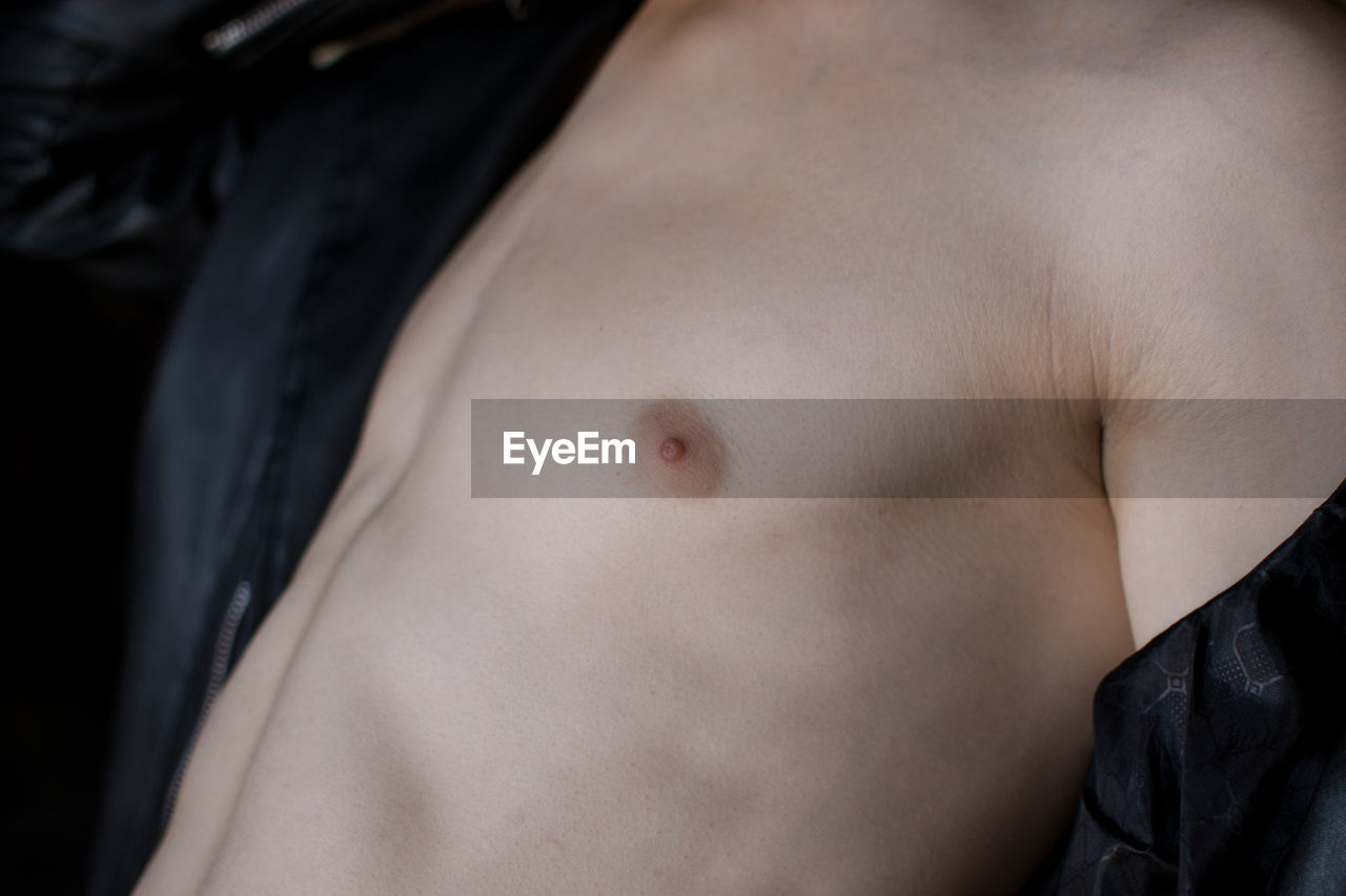 human skin, skin, human body part, midsection, one person, indoors, lifestyles, shirtless, close-up, adult, real people, body part, women, young adult, lying down, front view, chest, belly button, human body, black background, human limb
