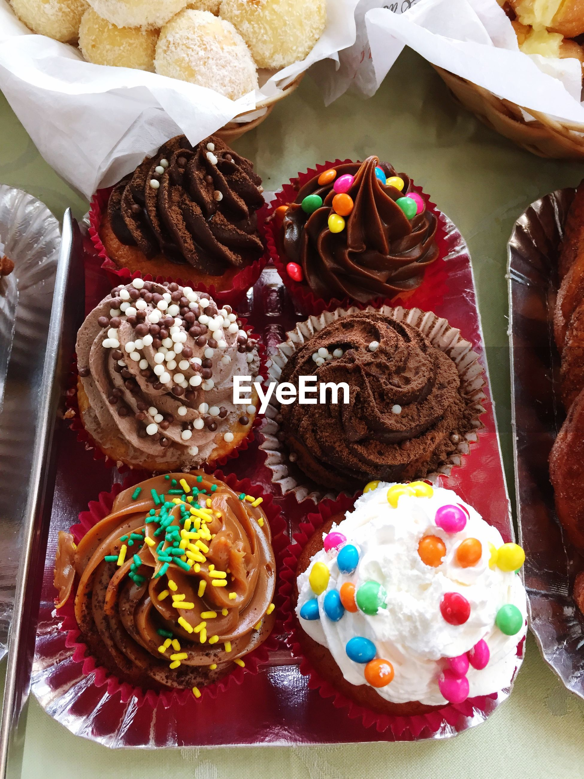 indoors, multi colored, sweet food, variation, still life, dessert, choice, large group of objects, freshness, indulgence, high angle view, unhealthy eating, food, arrangement, abundance, food and drink, ready-to-eat, cupcake, decoration, cake