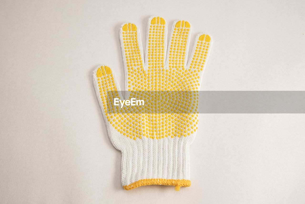 indoors, studio shot, yellow, white background, copy space, still life, textile, no people, glove, close-up, protective glove, cut out, pattern, protection, white color, high angle view, healthcare and medicine, single object, directly above, security, clean