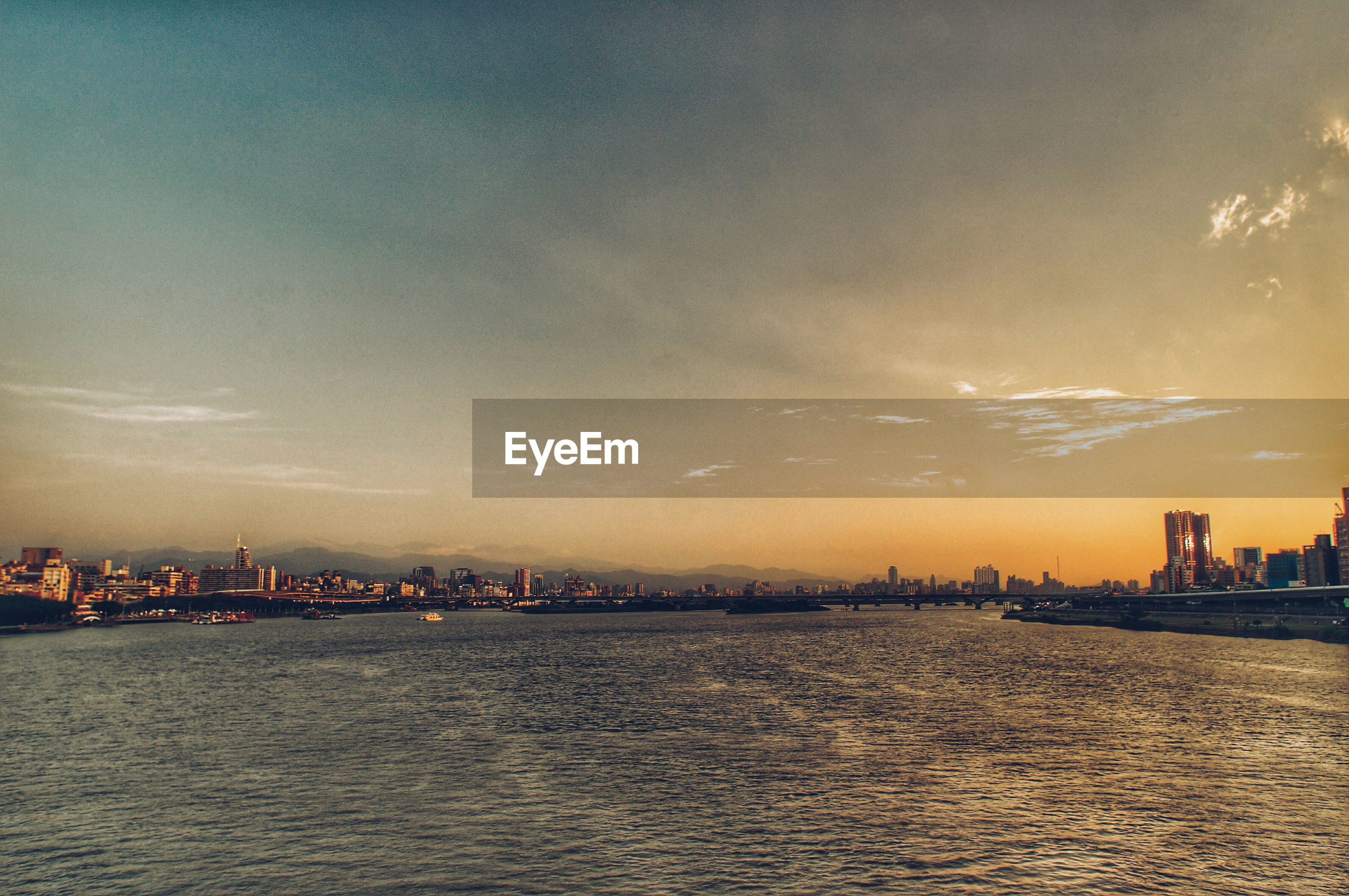 Scenic view of river by city against sky during sunset