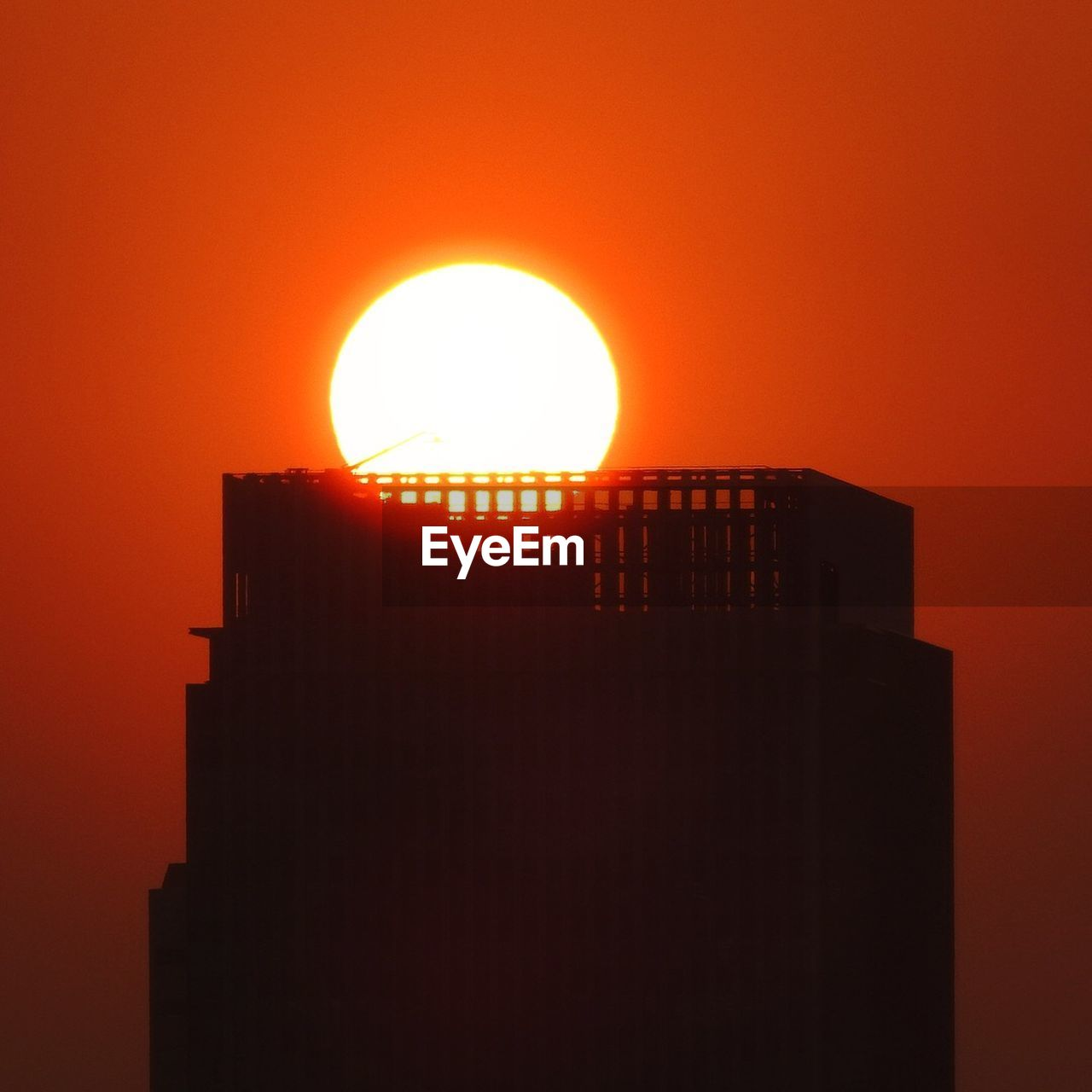 orange color, sunset, sun, architecture, built structure, sky, building exterior, silhouette, no people, nature, clear sky, low angle view, outdoors, copy space, sunlight, building, beauty in nature, scenics - nature, circle, geometric shape