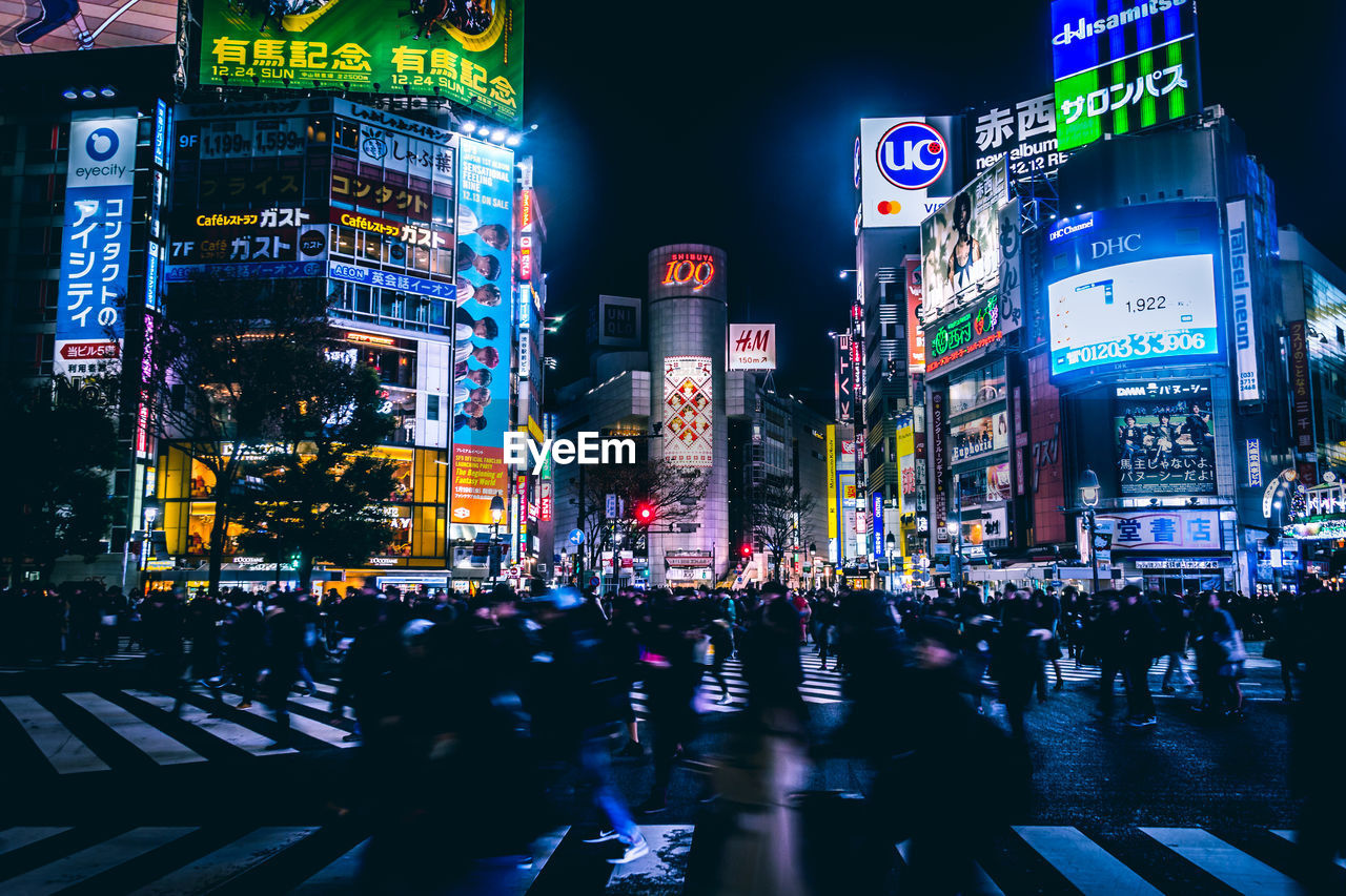 illuminated, city, building exterior, night, architecture, built structure, crowd, large group of people, group of people, advertisement, real people, street, city life, zebra crossing, crosswalk, crossing, building, city street, walking, road, outdoors, office building exterior, cityscape, skyscraper, financial district