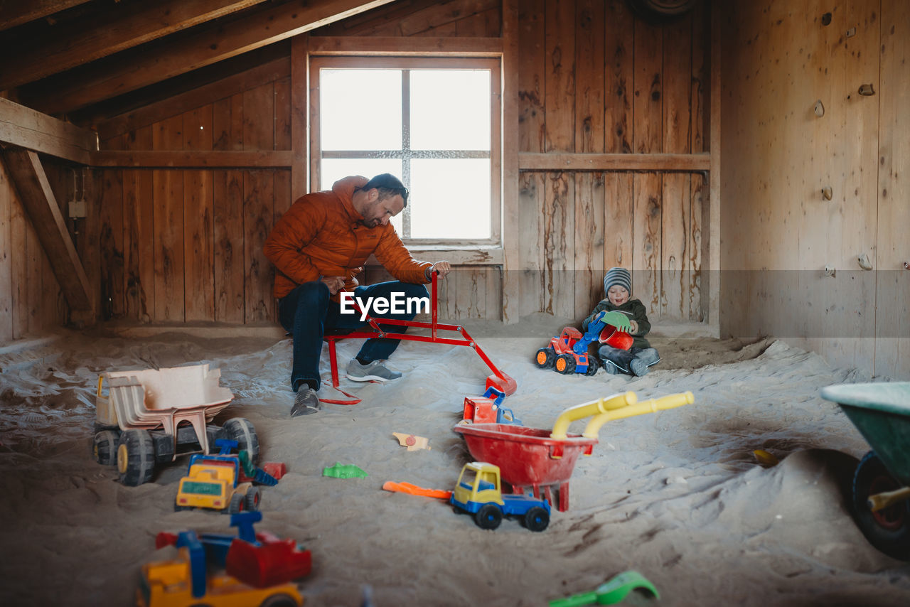 MAN WORKING WITH TOY ON FLOOR AT HOME