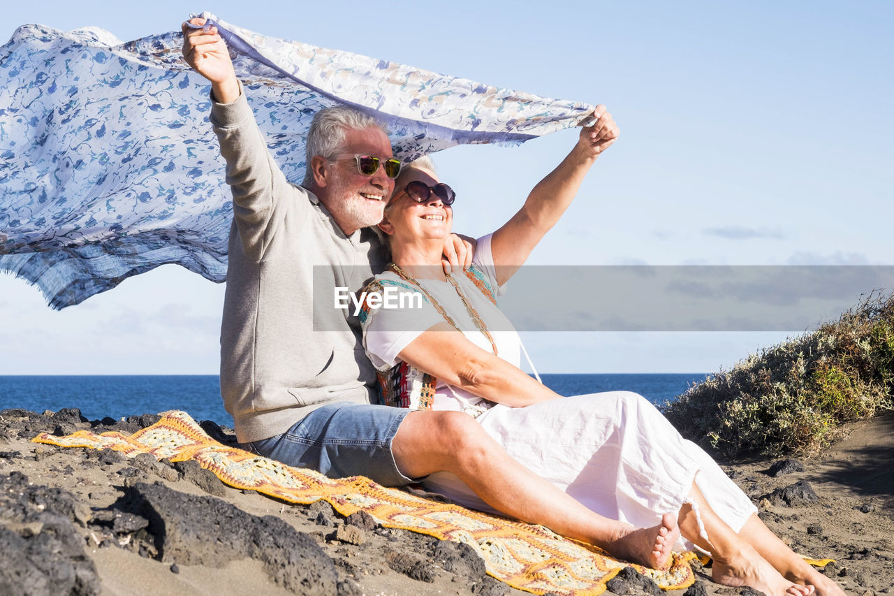 Happy Senior Couple With Scarf Sitting At Beach Against Sky