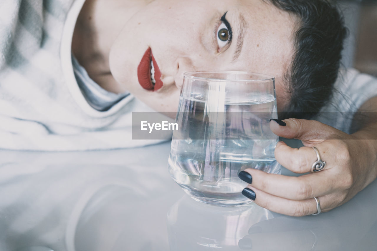 Close-up portrait of woman holding glass of water