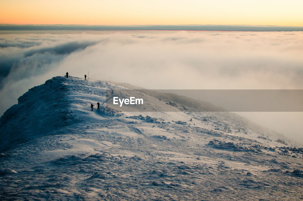 Scenic View Of Snow Covered Mountain By Cloudscape Against Sky During Sunset
