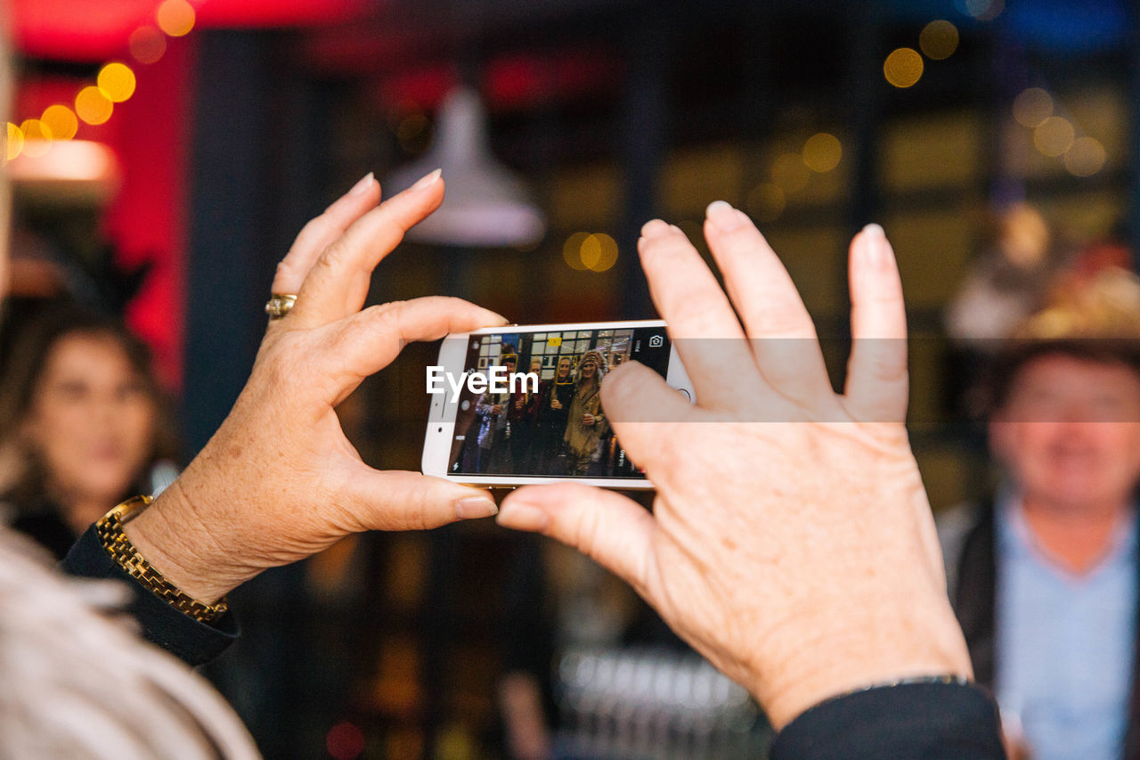 human hand, hand, wireless technology, men, real people, focus on foreground, technology, holding, human body part, photography themes, photographing, communication, group of people, lifestyles, people, leisure activity, smart phone, adult, mobile phone, activity, finger