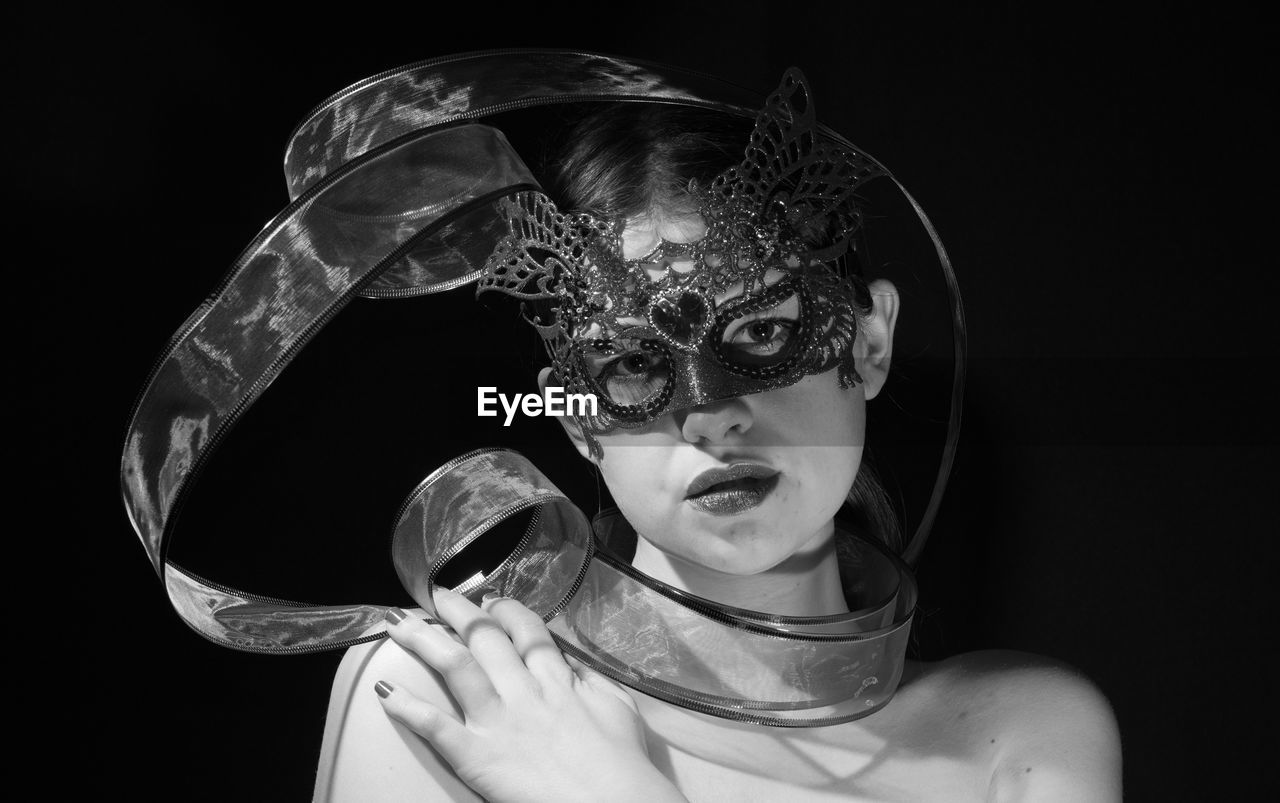 Portrait Of Woman Wearing Mask Against Black Background